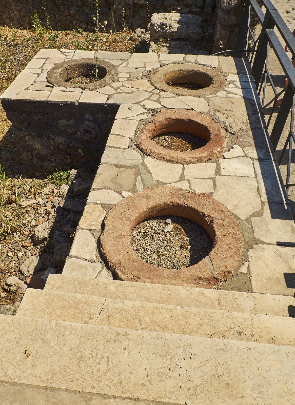 Kolorowa ilustracja przedstawia aktualny stan zabudowań Pompejów. Na fotografii ukazano szeroki kamienny mur, na którym widoczne są omurowane okrągłe otwory, być może są to paleniska.
