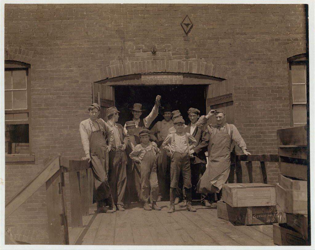 Grupa pracowników huty szkła Grupa pracowników huty szkła–najmniejszy na fotografii chłopiec jest zPolski inie zna angielskiego Źródło: Lewis Wickes Hine, Grupa pracowników huty szkła, 1910, fotografia, Biblioteka Kongresu USA, domena publiczna.
