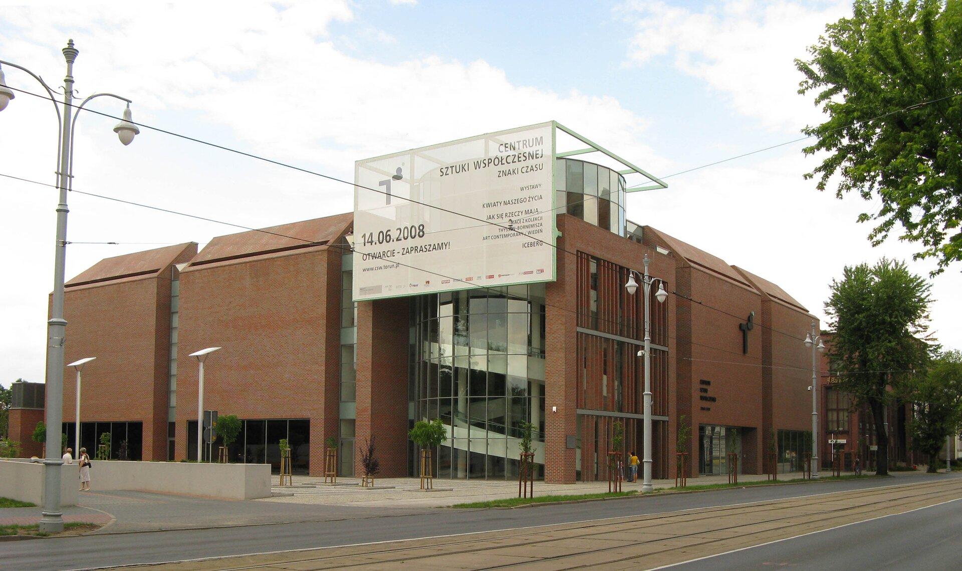 """Ilustracja przedstawia Centrum Sztuki Współczesnej Znaki Czasu wToruniu. Na zdjęciu ukazany jest nowoczesny budynek, którego prosta bryła łączy wsobie czerwoną cegłę zelementami szkła.  Wsześcienne formy elewacji wpisany jest walec oszklonej klatki schodowej, nad którą umieszczony został na ażurowej konstrukcji, biały baner znapisem: """"CENTRUM SZTUKI WSPÓŁCZESNEJ ZNAKI CZASU, 14.06.2008, OTWARCIE – ZAPRASZAMY"""". Budynek ustawiony jest wprzestrzeni miejskiej, przed nim znajduje się szeroka jezdnia ztorami tramwajowymi oraz duża, szara, ozdobna lampa uliczna."""