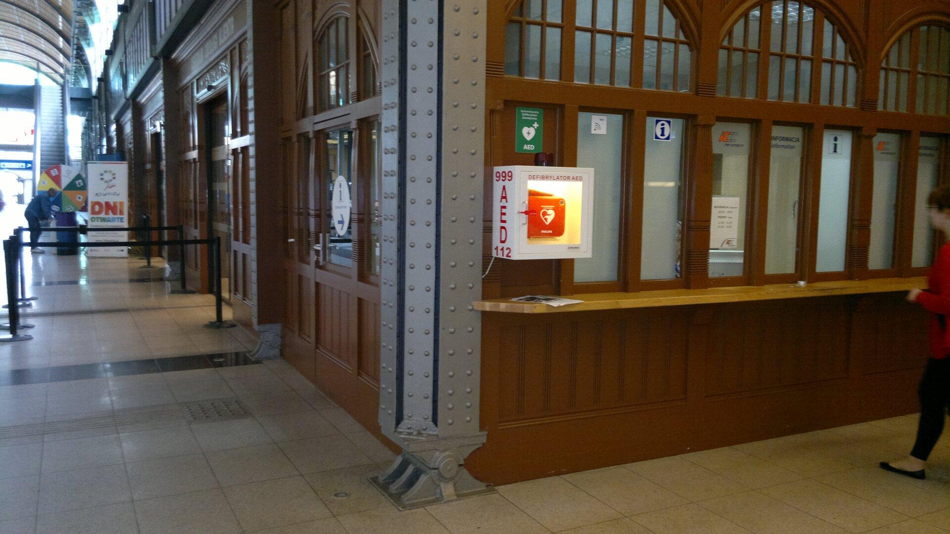 Kolorowe zdjęcie przedstawia fragment dworca kolejowego we Wrocławiu. Na pierwszym planie okienka znalepkami informacja. Na lewo od okienek, na rogu ściany, mała biała oszklona szafka zdefibrylatorem wewnątrz. Szafka wkształcie prostopadłościanu, oświetlona wewnątrz. Wymiary to 50 centymetrów wysokość i20 centymetrów głębokość szafki. Na lewym boku szafki czerwony napis AED oraz numery telefonów. Na górze 999, na dole 112. Za rogiem ściany kasy biletowe. Kasy umieszczone jedna za drugą wzdłuż ściany budynku. Kasy znajdują się wgłębi budynku. Wszystkie ściany wykonane są zciemnobrązowego drewna. Okienka wkształcie pionowych prostokątów. Każde trzy okienka zakończone zwieńczającym półokrągłym oknem powyżej.