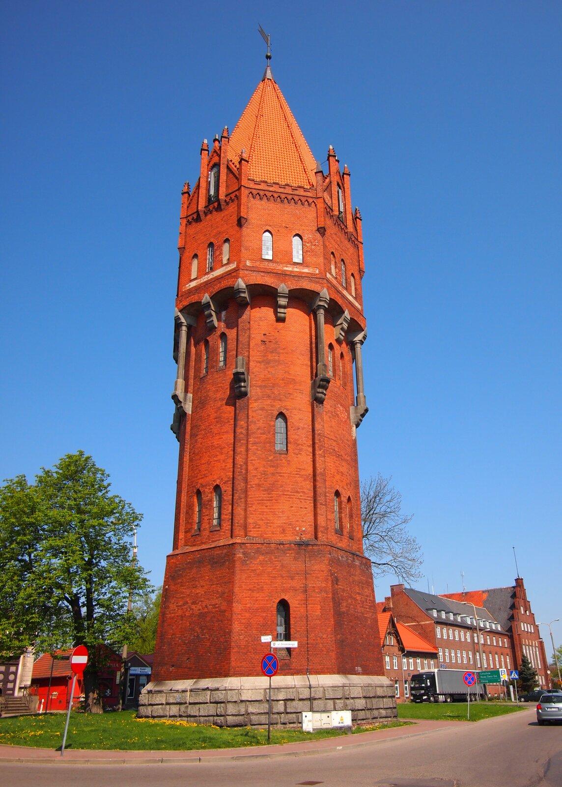 Zdjęcie przedstawia wieżę ciśnień. Wieża zajmuje całą wysokość zdjęcia. Zbudowana zczerwonej cegły. Ozdobnie wykończona. Wtle błękitne niebo. Zlewej stronie wieży zielone drzewo liściaste Zprawej strony, wtle, budynek zczerwonej cegły. Tuż przed wieżą ulica.