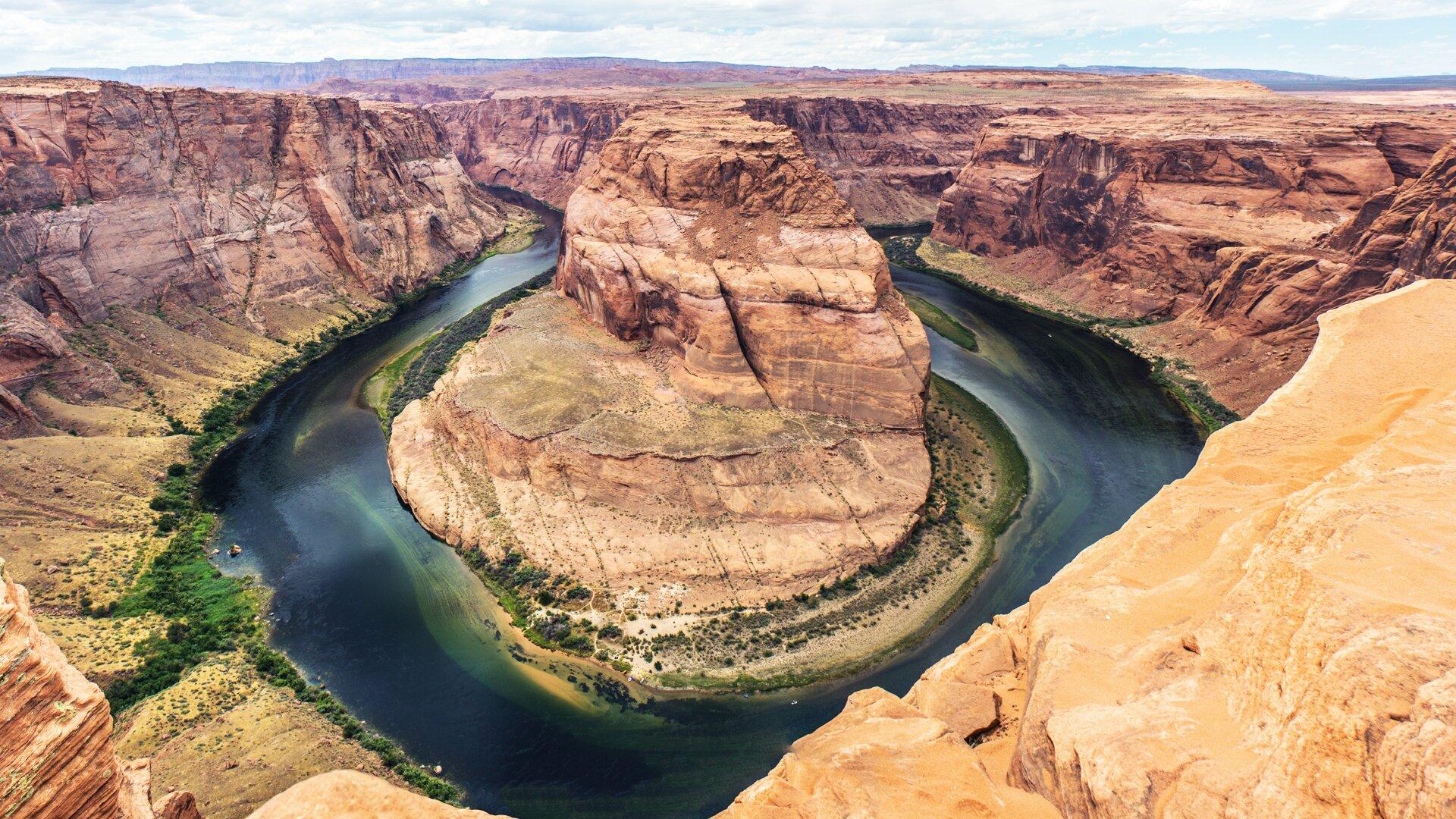 Zdjęcie przedstawia skalistą, jałową, bez roślinności równinę. Równina przecięta jest kanionem przez który płynie rzeka. Zdjęcie zrobione jest zwysokiego brzegu. Wcentrum fotografii pokazany jest meander jaki tworzy rzeka opływając wysoki skalisty cypel. Wody rzeki mają kolor ciemnoniebieski. Brzegi rzeki są zielone, porośnięte niską roślinnością. Widać przekrój skał na ścianach kanionu.