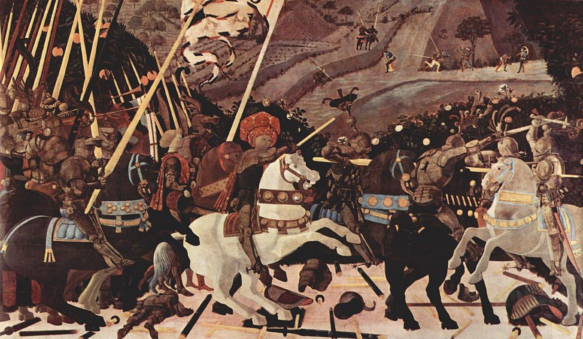 """Ilustracja przedstawia obraz Paola Uccella """"Bitwa pod San Romano"""". Wcentralnej części obrazu, na białym koniu wojskami Florencji dowodzi kondotier Niccolò da Tolentino, dosiadający białego, stającego dęba konia. Mężczyzna ma na sobie rycerską zbroję iturban. Wprawej dłoni trzyma laskę dowódczą. Za nim na koniach podąża grupa uzbrojonych wlance rycerzy. Jeden znich trzyma sztandar. Pomiędzy rycerzami młodzieńcy dmą wtrąby. Po prawej stronie pomiędzy wojskami toczy się walka. Scena rozgrywa się na tle wzgórza, na którym polują myśliwi. Woddali znajdują się dwaj rycerze na koniach."""