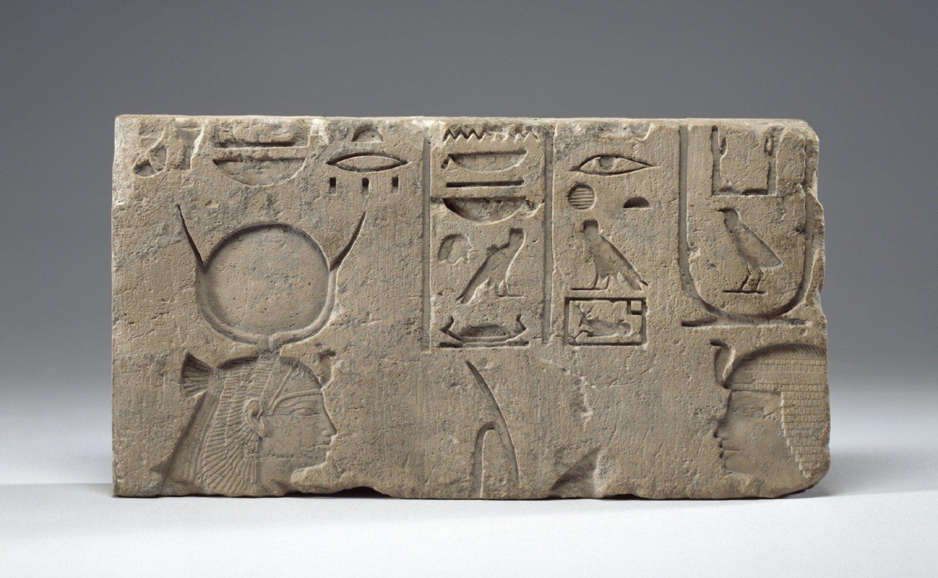 Ilustracja przedstawia starożytny relief ukazujący Hathor iKing Necho II. Na zdjęciu znajduje się kamienny blok zwyrytą wnim wklęsłą płaskorzeźbą. Wdolnej jego partii wyrzeźbione zostały głowy władców, nad nimi umieszczono egipskie hieroglify.