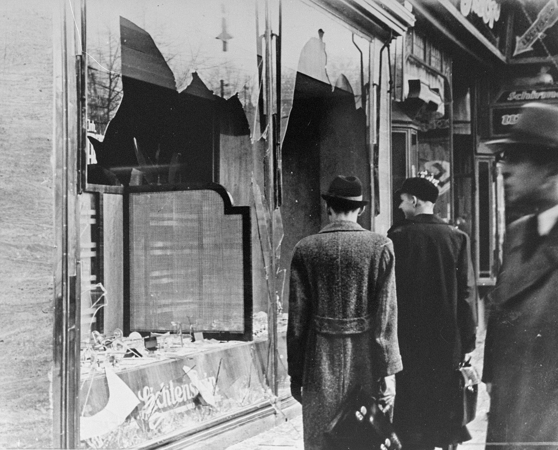"""Wybite okno sklepu żydowskiego, które zostało zniszczone wczasie Nocy Kryształowej. Niszczenie żydowskich sklepów isynagog podczas tzw. """"nocy kryształowej"""" 9/10 listopada 1938 roku. Źródło: Wybite okno sklepu żydowskiego, które zostało zniszczone wczasie Nocy Kryształowej., 1938, fotogafia, domena publiczna."""