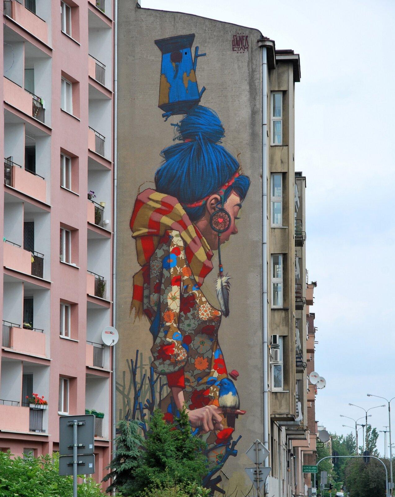 Mural przedstawiający dziewczynę wkoku zniebieskich włosów, ubraną wkolorową bluzkę wkwiaty.