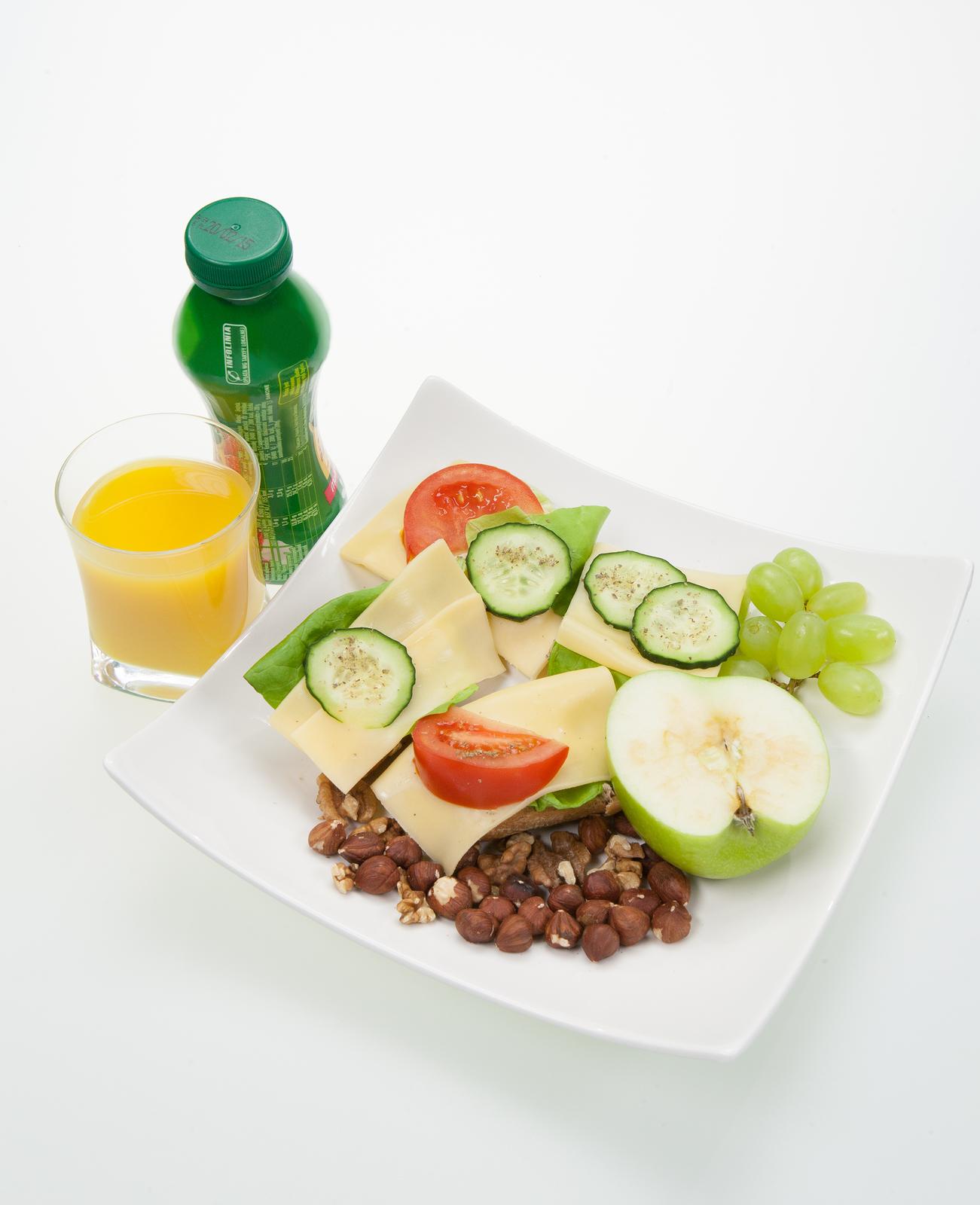 Fotografia przedstawia przygotowany posiłek śniadaniowy. Na talerzu znajdują się kanapki zpełnoziarnistego pieczywa, zserem iwarzywami, atakże owoce iorzechy. Obok talerza stoi plastikowa butelka zjogurtem, atakże szklanka napełniona sokiem owocowym.