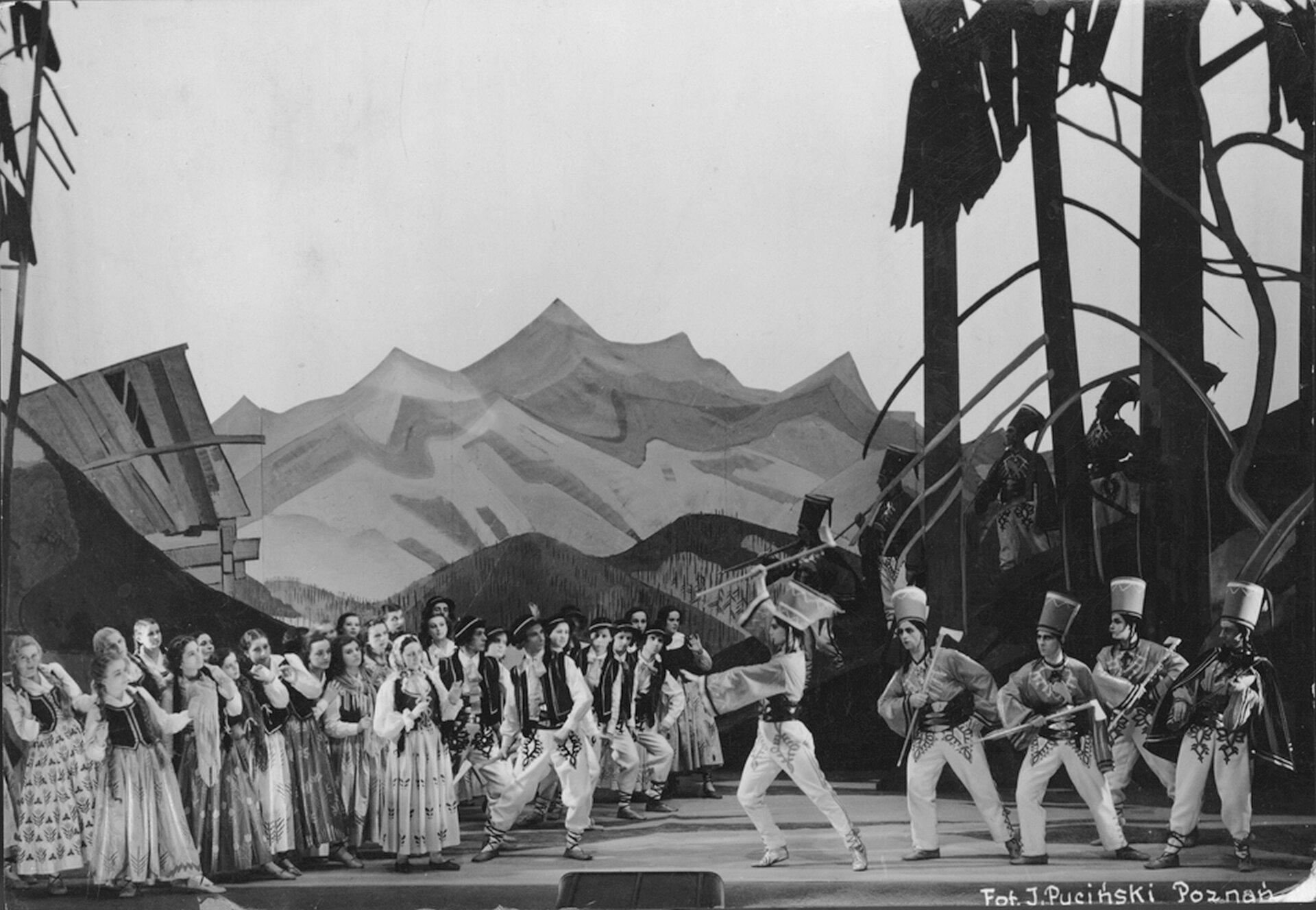 """Ilustracja przedstawia """"Harnasie"""" Karola Szymanowskiego na scenie Teatru Wielkiego wPoznaniu. Fotografia ukazuje damskie imęskie postacie ubrane wstroje podhalańskie."""