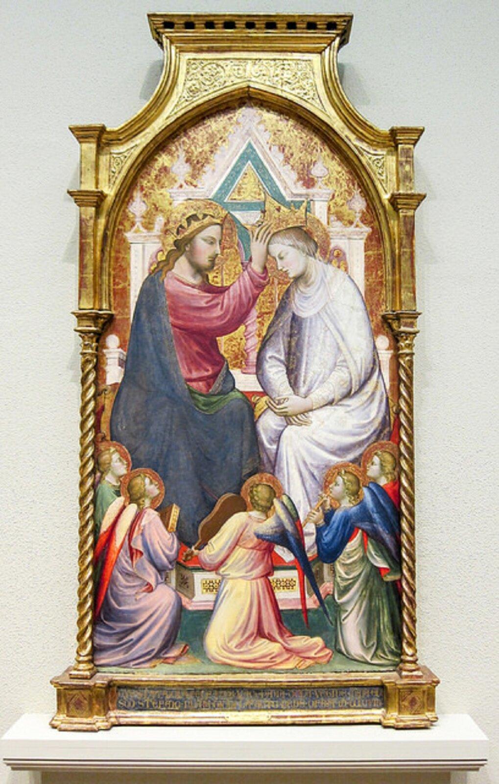 """Ilustracja przedstawia dzieło Mariotta di Narda, """"Koronacja Najświętszej Maryi Panny zpięcioma muzykującymi aniołami"""". Jest częścią nadstawy ołtarzowej. Obraz oprawiony jest warchitektoniczną ramę zdwiema skręconymi kolumienkami oraz prosto zakończoną górną częścią, wypełnioną złotymi ornamentami. Ma kształt pionowego prostokąta, zamkniętego łukiem ostrym. Ukazuje scenę koronacji Marii. Na tronie siedzi Jezus inakłada na głowę Matki koronę. Poniżej klęczy pięć aniołów, których głowy wzniesione są ku górze - patrzą na akt koronacji."""