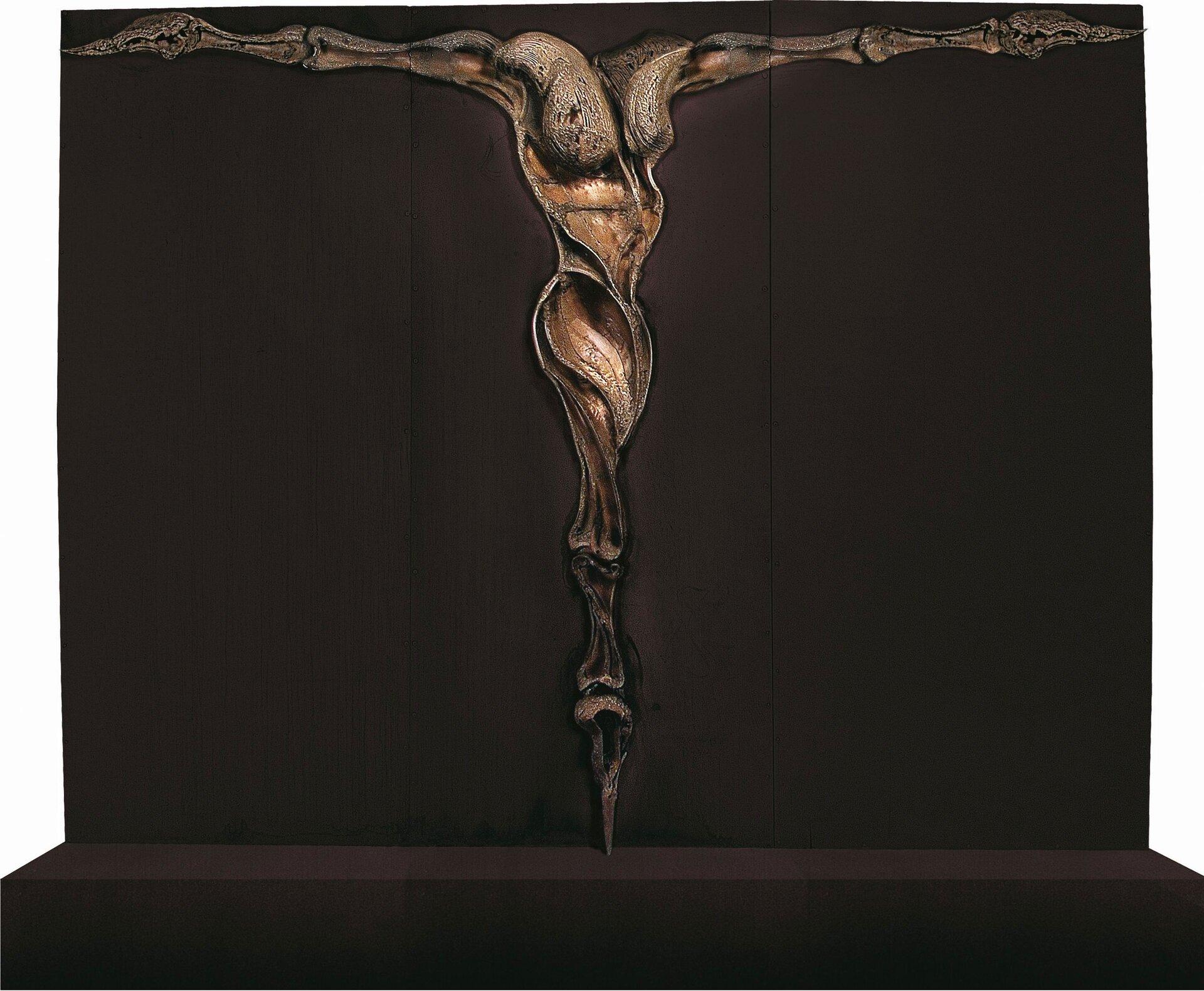 """Ilustracja przedstawia instalację """"Bez tytułu"""" autorstwa Anny Wysockiej. Zdjęcie ukazuje rzeźbę przypominającą postać zrozpostartymi rękoma, bez głowy, umieszczoną na brązowym podeście. Ramiona izłączone nogi mają formę połączonych piszczeli. Metaliczna, błyszcząca struktura obiektu wyłania się zbrązowego, matowego tła."""