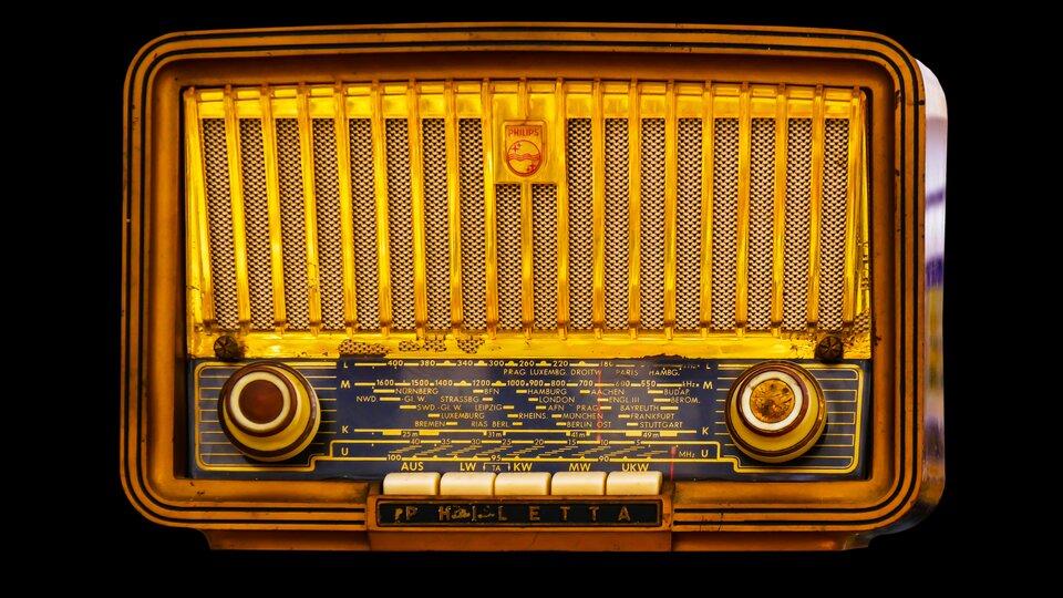 Na czarnym tle znajduje się zdjęcie zabytkowego radia. Ma ono drewnianą obudowę. Wewnątrz, tuż za złotym ożebrowaniem, umocowana jest metalowa siatka. Wdolnej części radia umieszczono granatowy panel, ana nim żółte napisy idwa duże pokrętła. Pomiędzy nimi znajduje się pięć białych klawiszy.