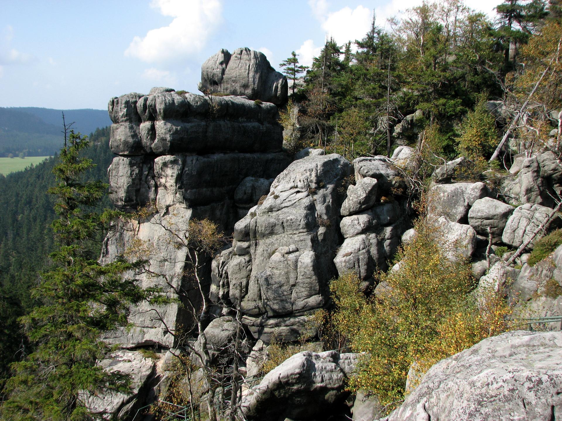 Fotografia przedstawia szare, spękane skały porośnięte drzewami. To rezerwat krajobrazowy Szczeliniec Wielki wGórach Stołowych wwojewództwie dolnośląskim.