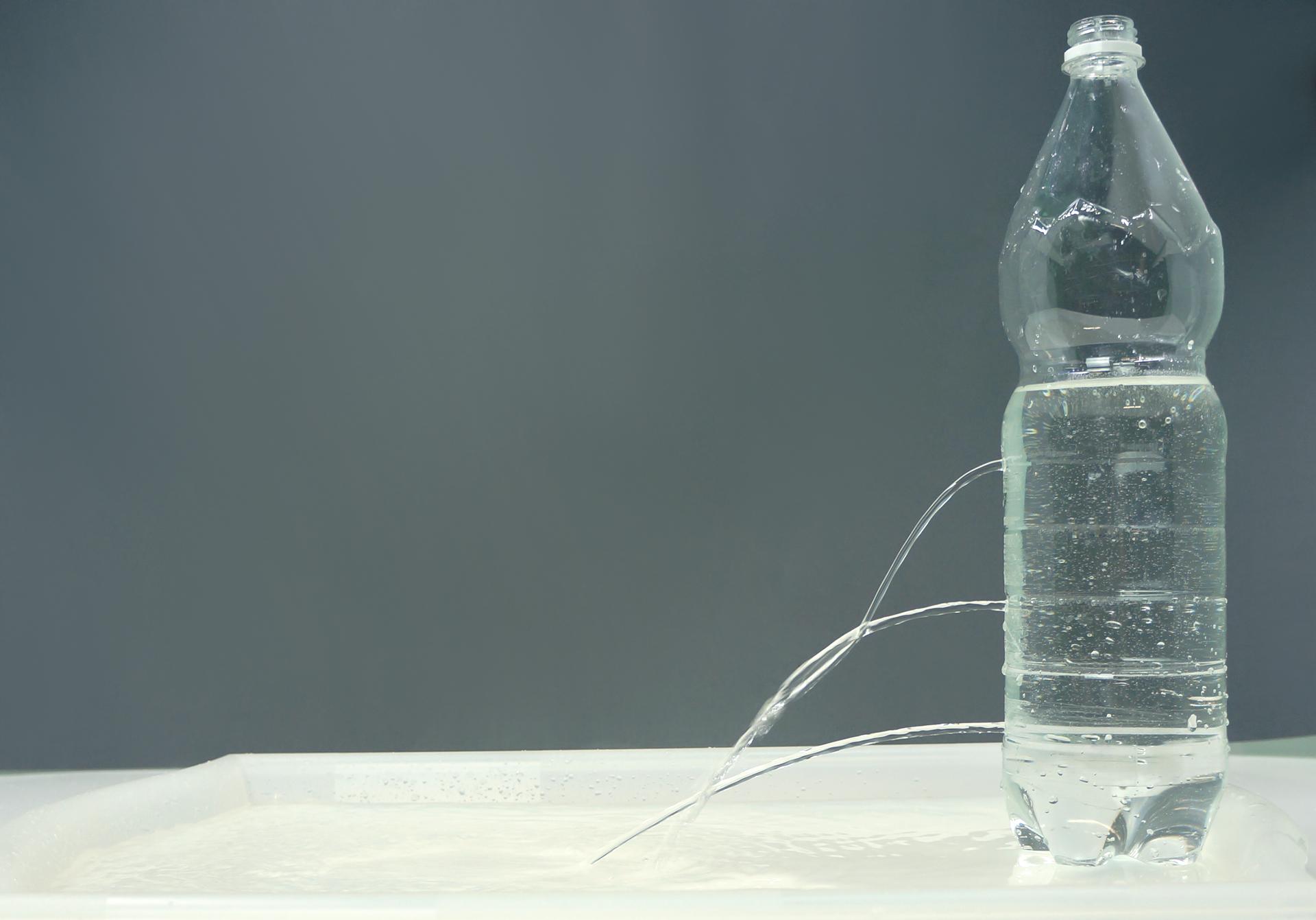 Zdjęcie przedstawiające butelkę wypełnioną wodą, przedziurawioną wtrzech miejscach. Strumienie wypływającej wody posiadają różne ciśnienie wzależności od wysokości słupa wody wbutelce.
