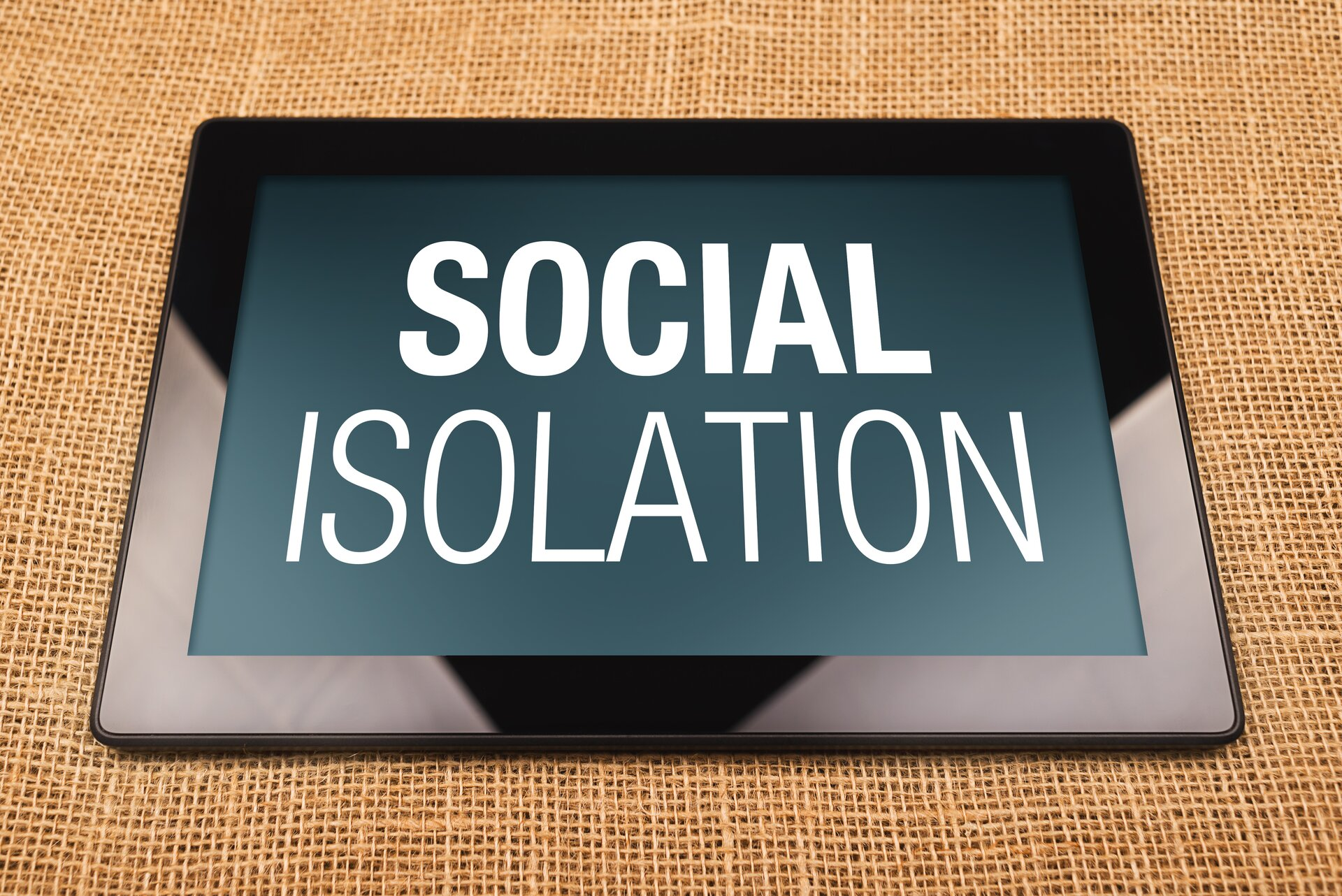 Ilustracja przedstawia cyfrowe wykluczenie. Ukazuje ona tablet znapisem na wyświetlaczu SOCIAL ISOLATION.