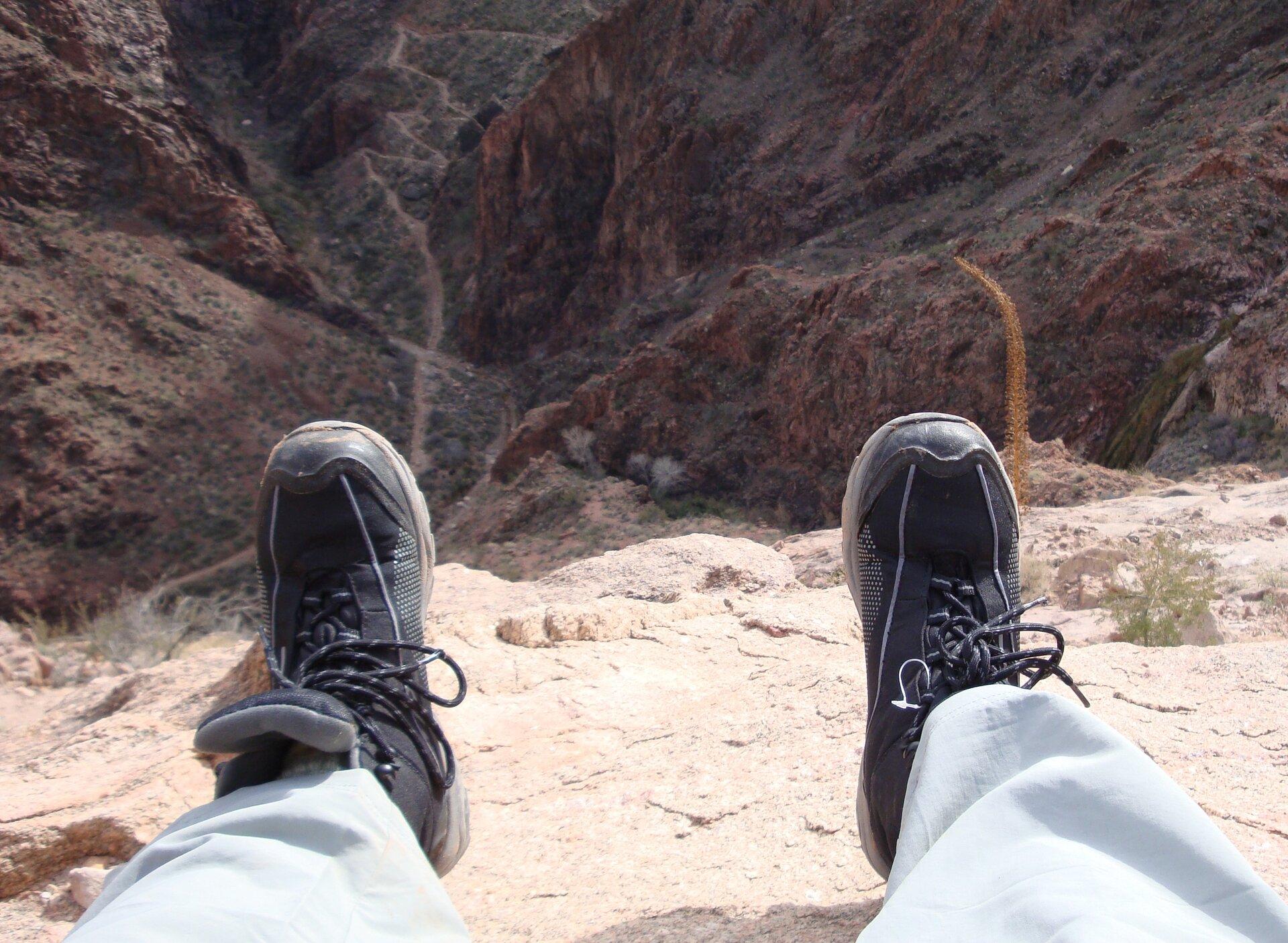 na zdjęciu, na pierwszym planie widać nogi wsportowych butach, awgłębi Wielki Kanion