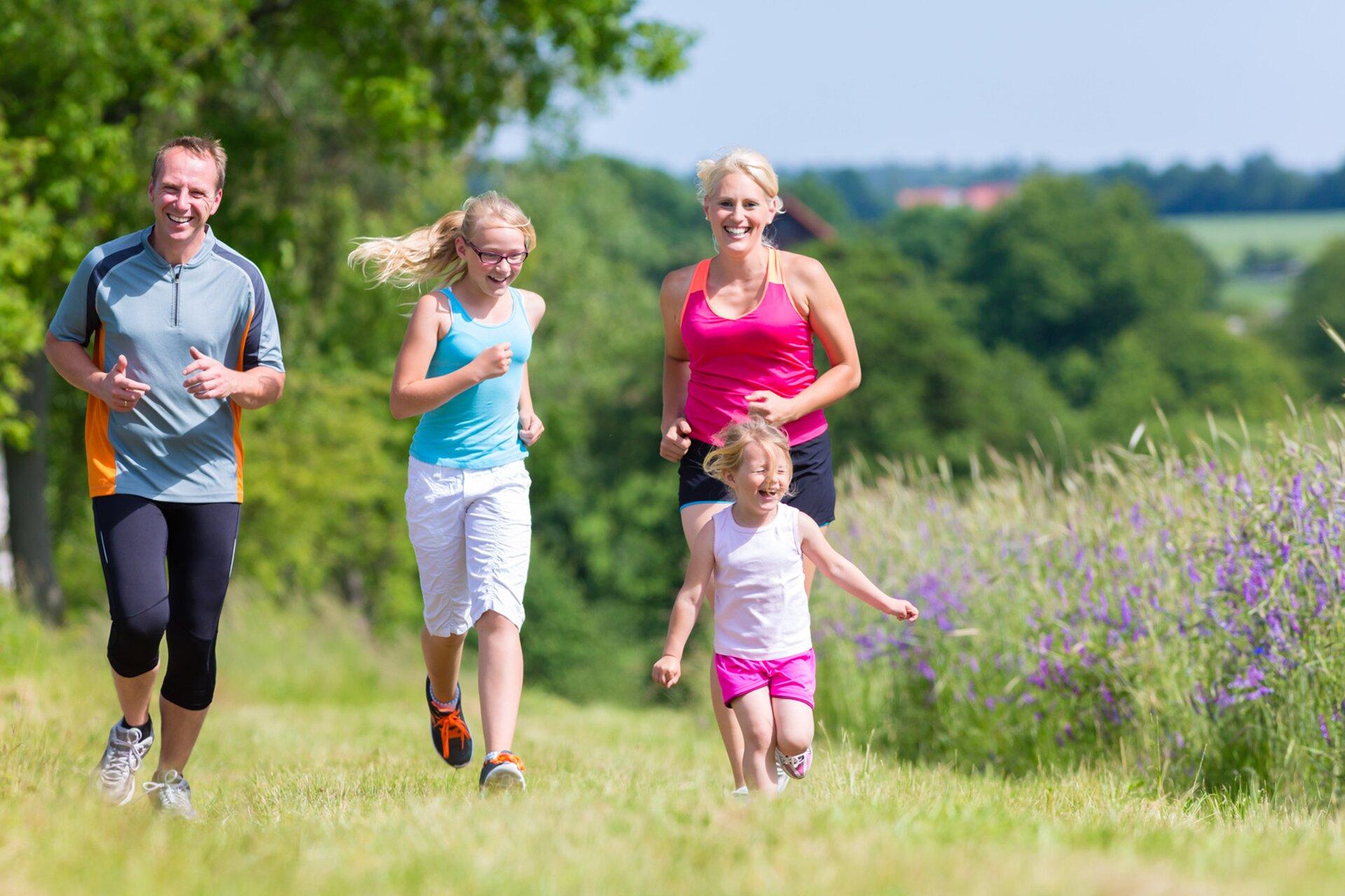 Fotografia przedstawia cztery uśmiechnięte osoby biegające po łące. Mężczyzna, dwie dziewczynki ikobieta są wyposażeni wsportowe obuwie ikrótkie ubranie do joggingu. Biegną po nasłonecznionej łące, wdłuż pola pokrytego zbożem, przeplatanym błękitnymi kwiatami. Na drugim planie drzewa zbujnymi koronami, pełnymi zielonych liści.