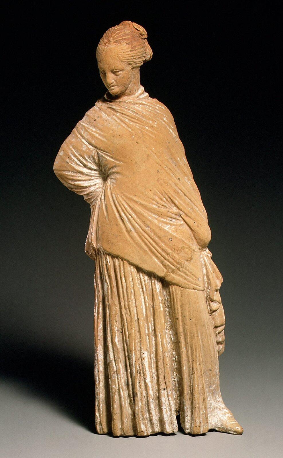 Fotografia nieznanego autora przedstawia rzeźbę stojącej kobiety. Włosy ma upięte wkok. Postać zgrymasem niezadowolenia spogląda wwprawo. Ubrana jest wdługą zakrywającą całe ciało szatę.