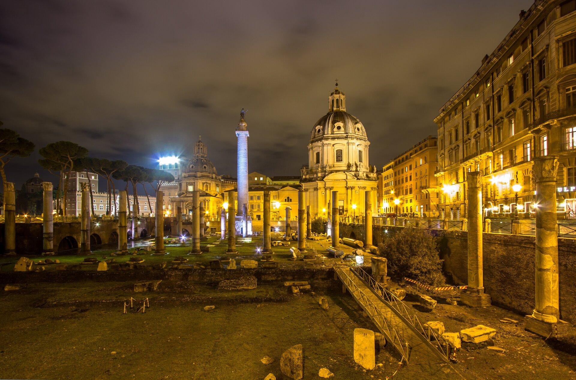 Fotografia nieznanego autora przedstawia widok na Forum Trajana wRzymie. Znajdują się na nim ruiny kolumnady. Wtle przedstawione są współczesne budynki. Zdjęcie wykonano wnocy.