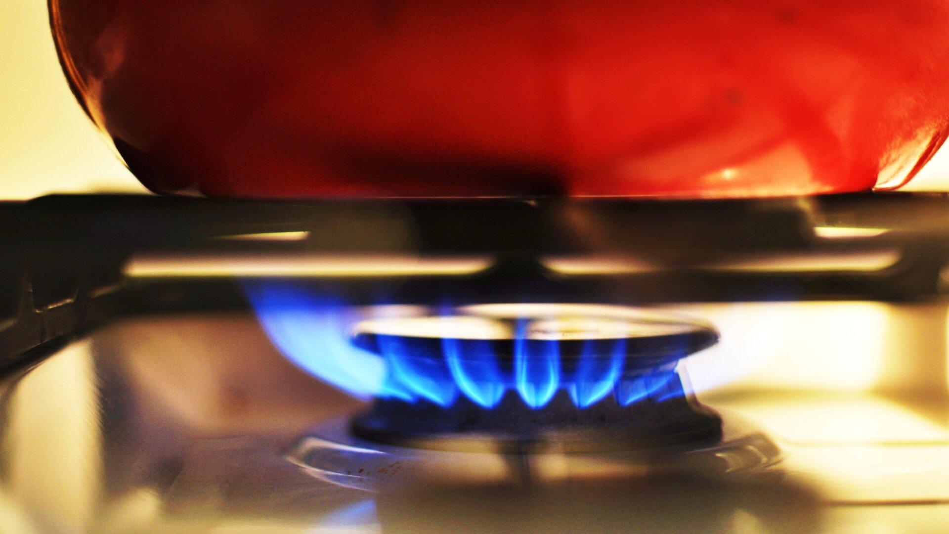 Ilustracja przedstawia naczynie postawione na włączony na kuchence gaz. Garnek ma kolor czerwony.