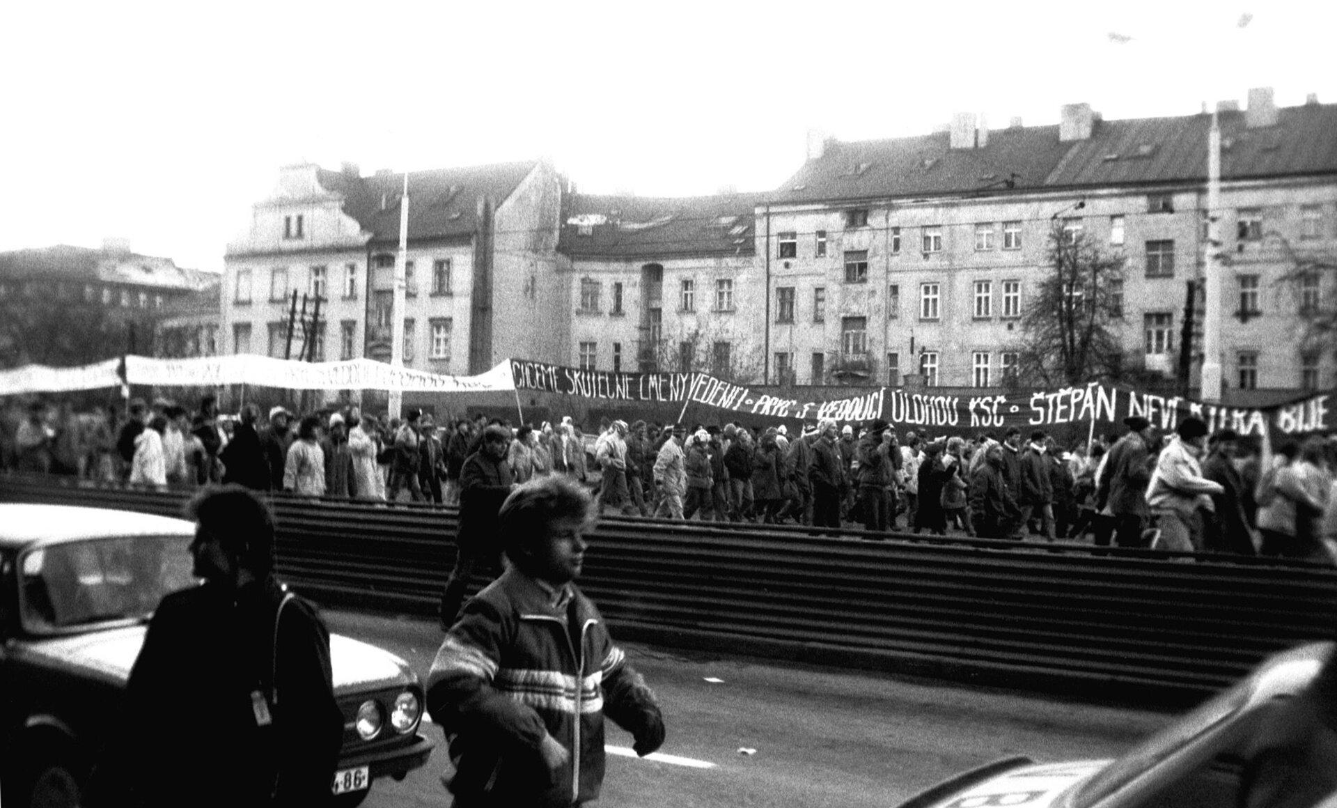 Na czarno-białym zdjęciu demonstracja. Tłum idzie ulicą, transparenty znapisami wjęzyku czeskim.