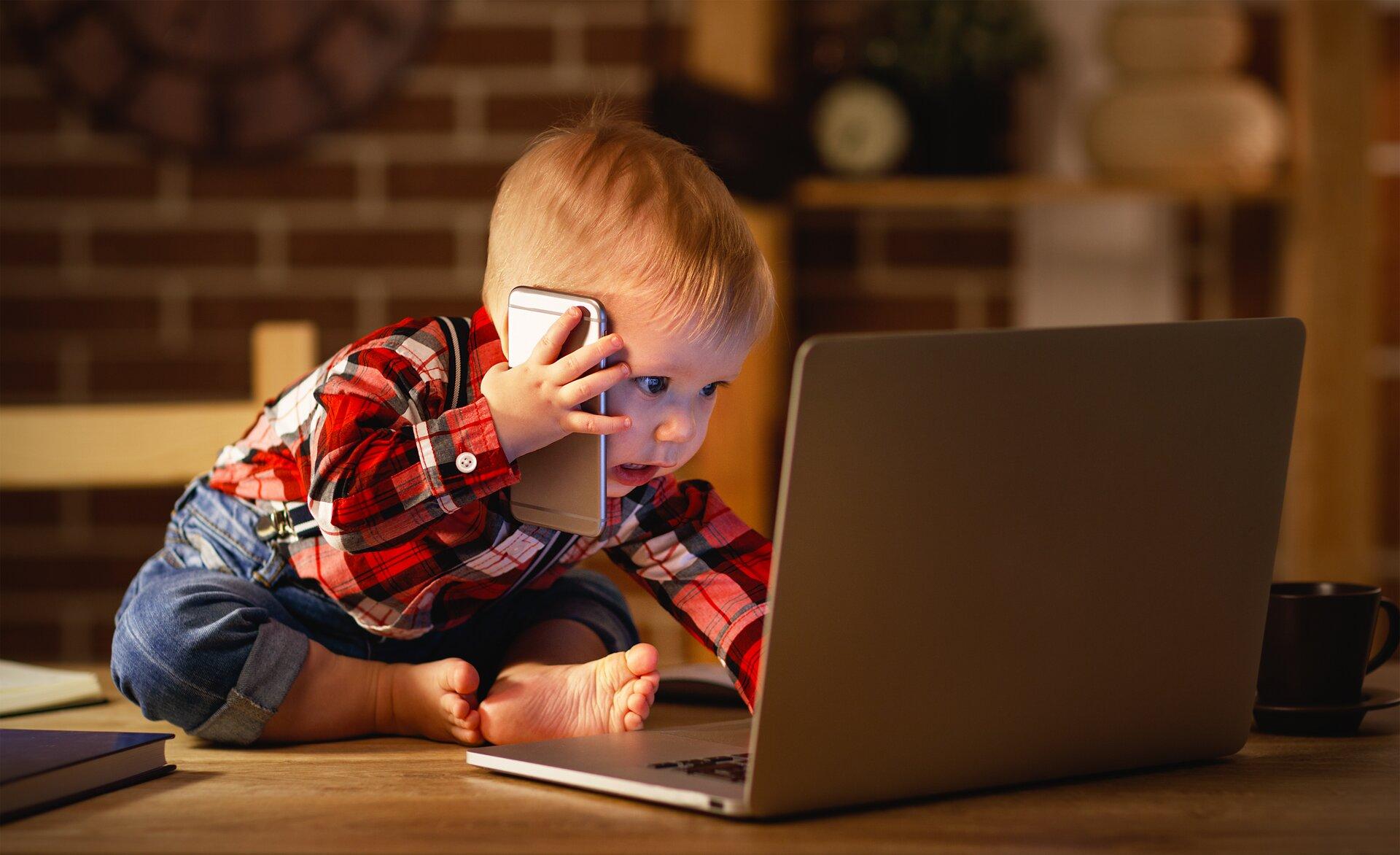 Ilustracja przedstawia dziecko wwieku przedszkolnym siedzące na stole przed otwartym laptopem. Lewą ręką klika wklawiaturę, wprawej ręce, przy uchu, trzyma telefon komórkowy.
