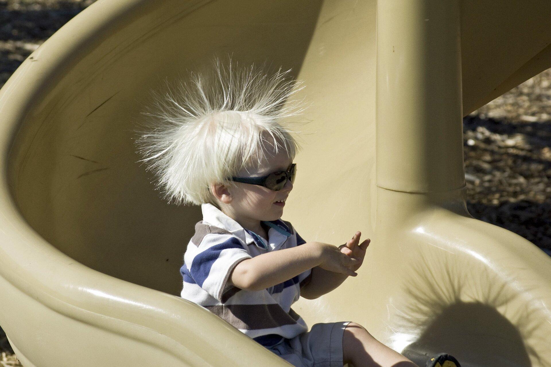 Zdjęcie przedstawia dziecko zjeżdżające po plastikowej zjeżdżalni rynnowej wkolorze kremowym. Chłopiec ma około pięć lat, jasne włosy iletnie ubranie. Krótkie włosy, bardzo mocno naelektryzowane sterczą mu na wszystkie strony.