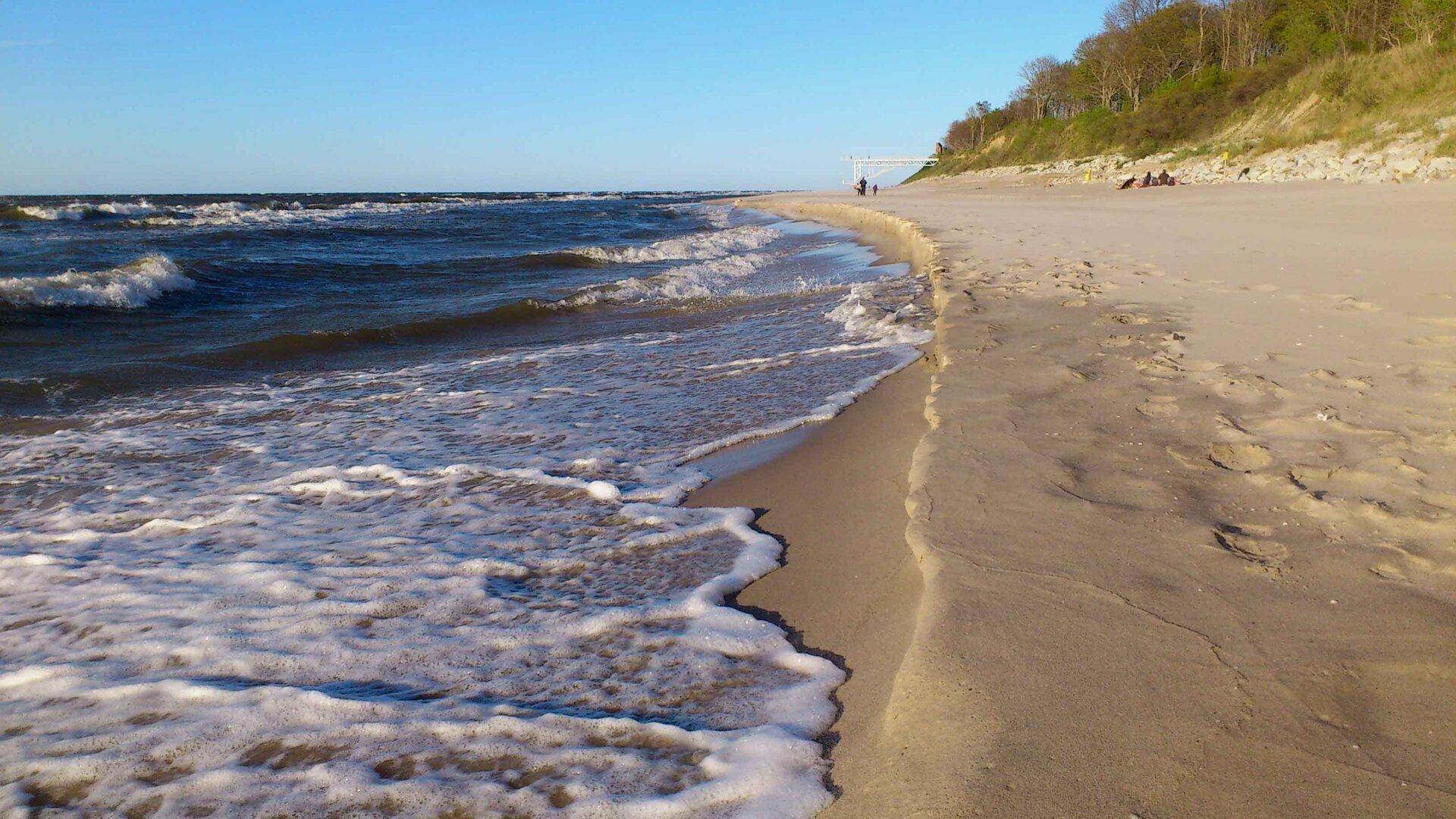 Na zdjęciu brzeg morza, fale, piaszczysta plaża, niewysokie wydmy porośnięte trawami ilasem.