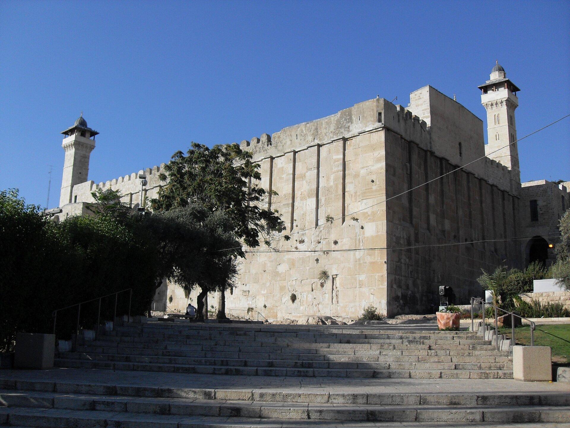 Ilustracja przedstawia fotografię symboliczne miejsce pochówku Abrahama, Sary, Izaaka, Rebeki, Jakuba iLei. Grafika przedstawia wysoki budynek zkamienia, który nie ma okien. Widoczne są dwie wierze po prawej ilewej stronie budowli. Do budynku prowadzą szerokie kamienne schody.