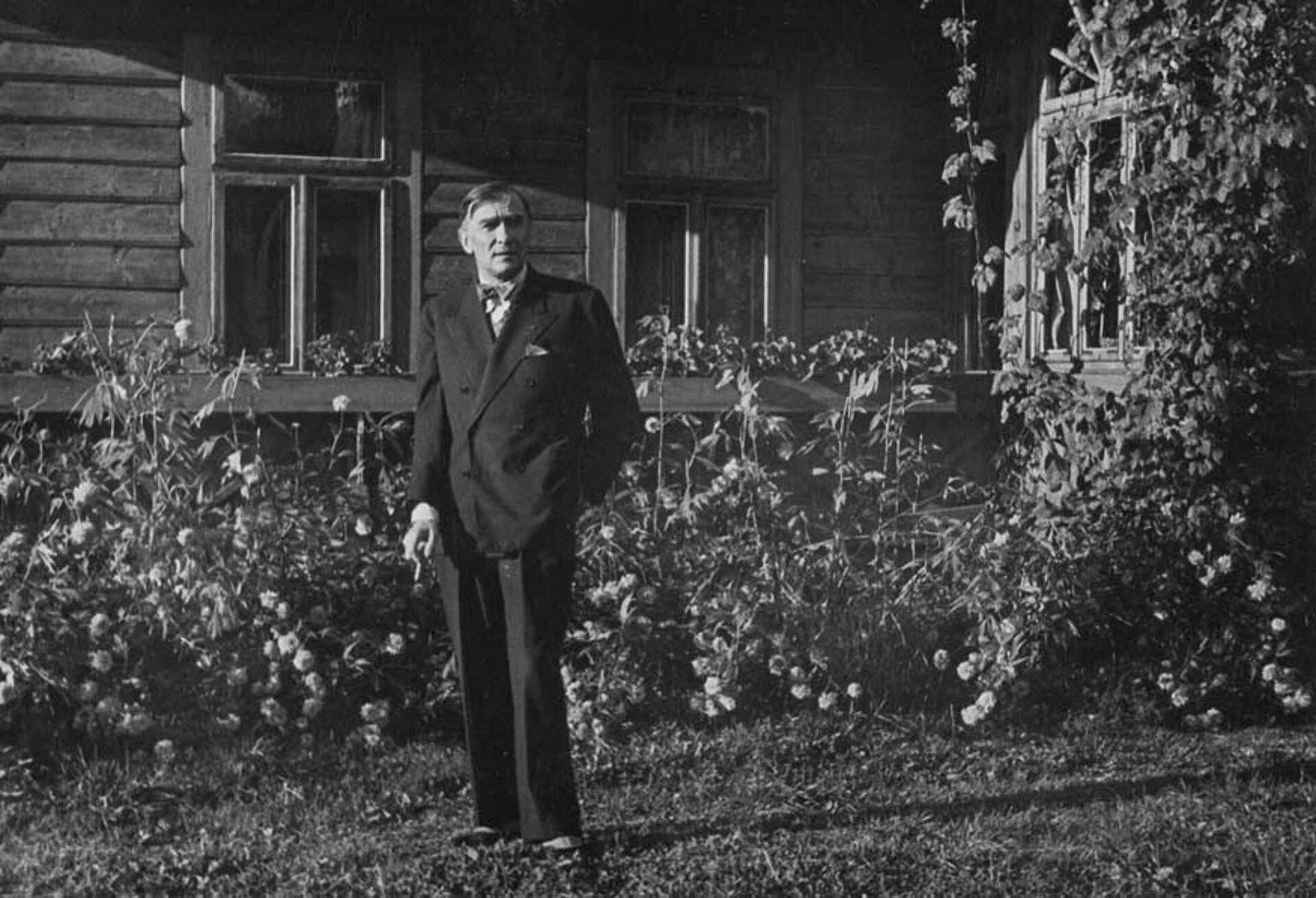 """Fotografia przedstawia Karola Szymanowskiego przed willą """"Atma"""" wZakopanem w1935 roku. Mężczyzna wśrednim wieku, ubrany wgarnitur. Wprawej dłoni trzyma papieros, lewą natomiast ma wkieszeni."""