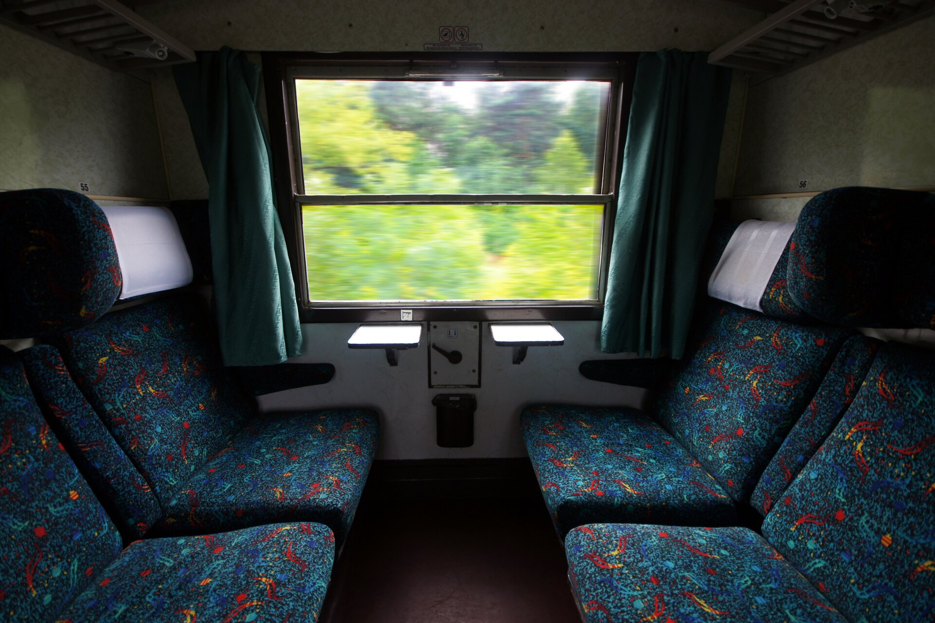 Zdjęcie przedstawia wnętrze przedziału wpociągu. Po lewej ipo prawej krzesła obite wielkokolorowym materiałem. Na wprost okno. Za oknem widać rozmazane kontury zielonych drzew.