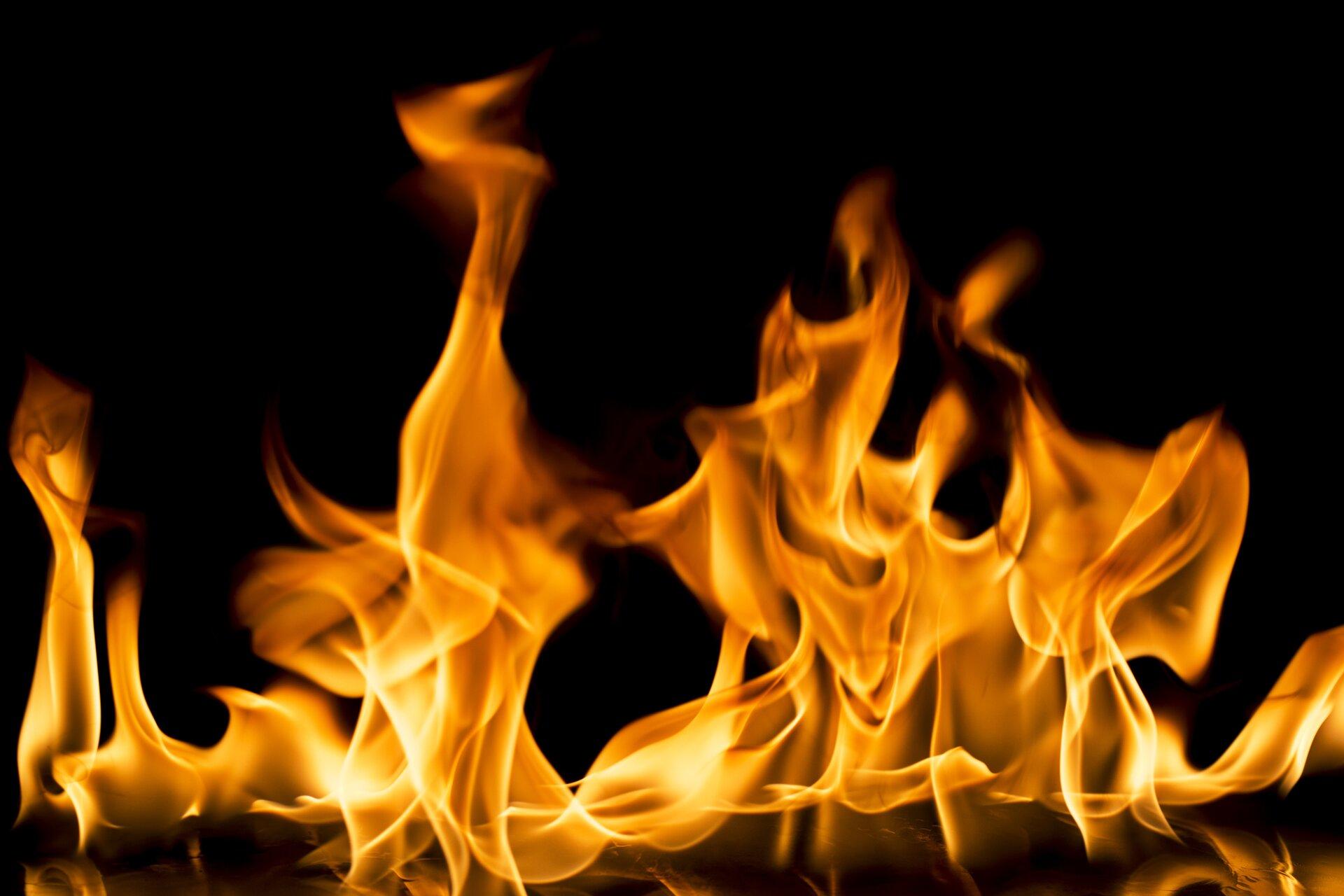 Ilustracja przedstawia ogień. Płomienie są wkolorze pomarańczowym oraz widzimy je na czarnym tle. Ogień jest jednym zfundamentalnych odkryć okresu prehistorii. Jest to zjawisko towarzyszące fizyczno-chemicznemu procesowi spalania.