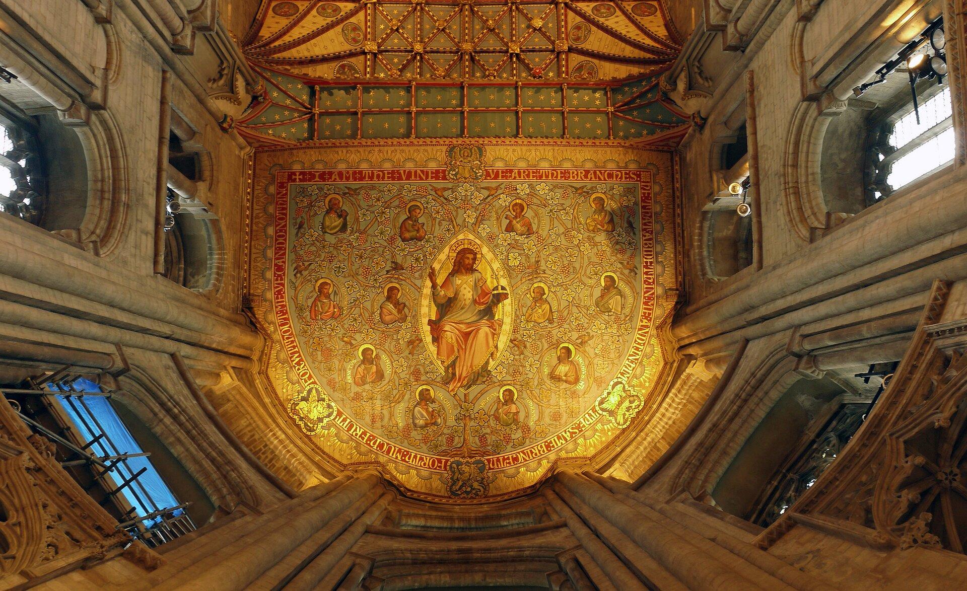 Ilustracja przedstawia sufit Katedry św. Piotra, Pawła iAndrzeja wPeterborough. Wcentralnej części sufitu, na złotym, wzorzystym tle namalowany jest Jezus na tle mandorli wkształcie migdała. Otaczają go postacie dwunastu apostołów. Scena zamknięta jest dekoracyjną bordiurą ze złotymi napisami na czerwonym tle. Po bokach znajdują się perspektywicznie ujęte okna, które przedzielają wiązki służek.