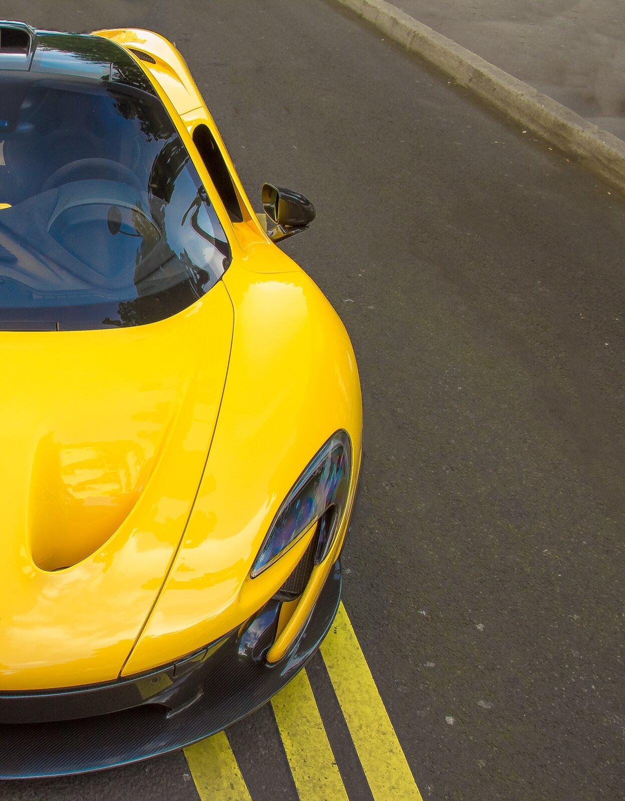 Zdjęcie przedstawia fragment sportowego samochodu. Samochód koloru żółtego, błyszcząca karoseria. Stoi na szarej, asfaltowej drodze.