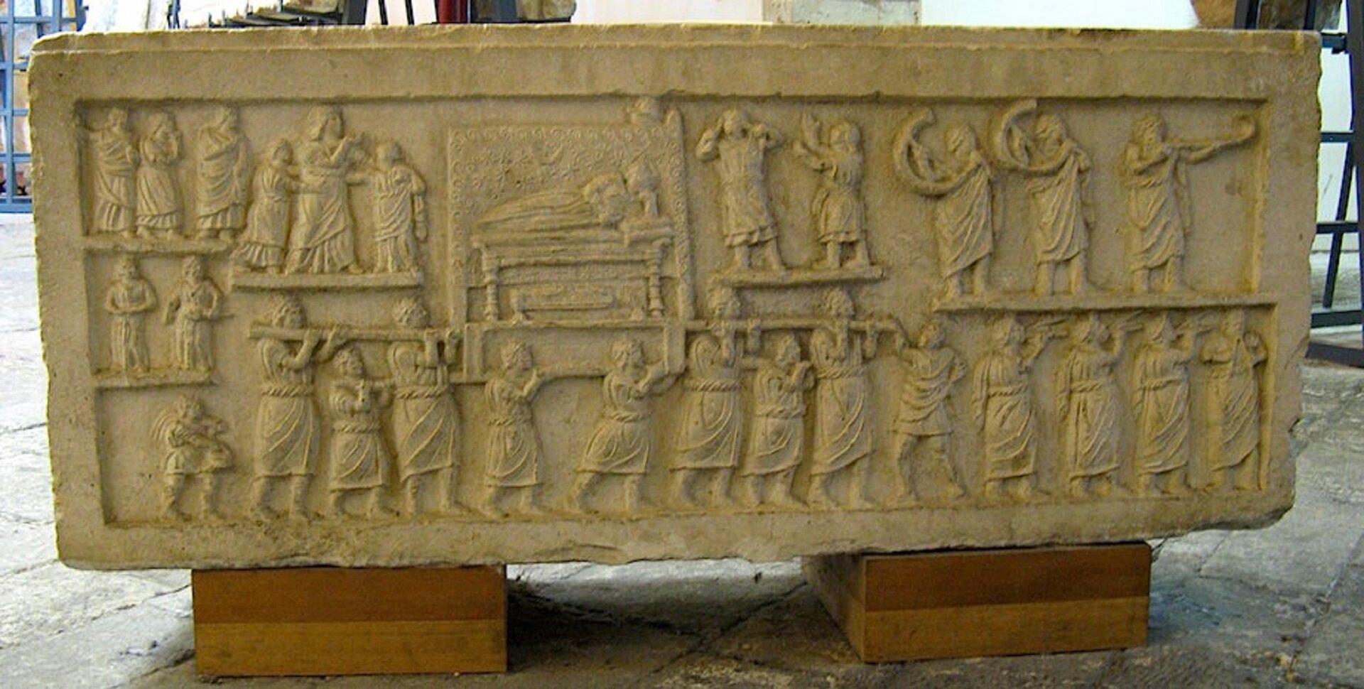 """Ilustracja przedstawia rzeźbę """"Kondukt pogrzebowy"""". Rzeźba ukazuje kondukt pogrzebowy, czyli grupę ludzi, którzy idą niosąc ciało. Dookoła są postaci przyglądający się konduktowi."""