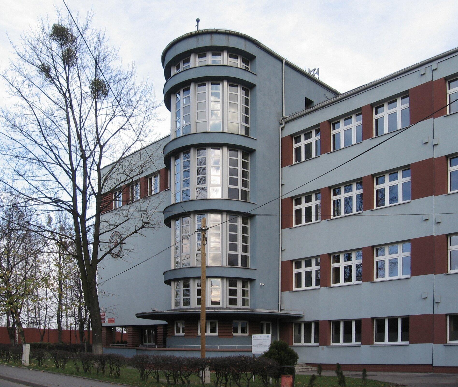 Ilustracja przedstawia budynek szkoły wPiekarach Śląskich-Szarleju. Na zdjęciu ukazana jest frontalna część prostej budowli, wktórej sześcienną formę została wpisana półokrągła, oszklona, pięciokondygnacyjna bryła, wysuwająca się zfasady. Elewacja szkoły pomalowana jest na szaro, płaszczyzny pomiędzy oknami na brązowo. Budynek stoi pośród drzew.