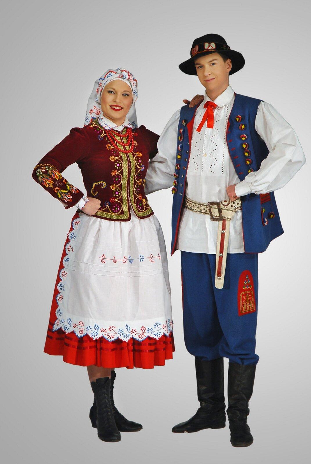 Na zdjęciu para ubrana wstrój rzeszowski. Chłopak ma filcowy kapelusz. Na płóciennej koszuli nosi długą do bioder niebieską kamizelkę bez rękawów zżółto - czerwonymi zdobieniami. Spodnie chłopaka uszyte są niebieskiej tkaniny iwpuszczone wwysokie kozaki zcholewami. Dziewczyna nosi na głowie kwiecistą chustę. Na białej koszuli ma sukienny kaftanik wbordowym kolorze, dopasowany wtalii ibogato zdobiony haftami. Czerwona, szeroka, bogato marszczona spódnica opasana jest fartuszkiem zwanym zapaską. Strój uzupełniają czarne wysokie trzewiki iczerwone korale.