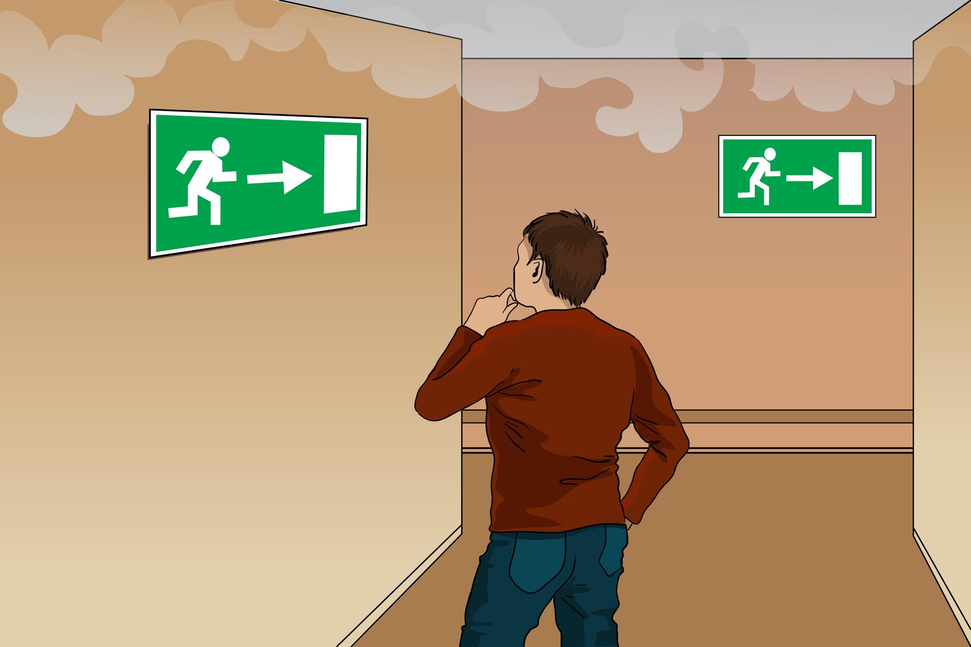 Rysunek przedstawia rozwidlający się na końcu korytarz ikłęby dymu unoszące się pod sufitem. Na pierwszym planie pokazany jest od tyłu uczeń patrzący na ścianę ztablicą informującą okierunku drogi ewakuacji. Na samym końcu korytarza wrozwidleniu identyczny znak wskazuje odnogę wprawo.