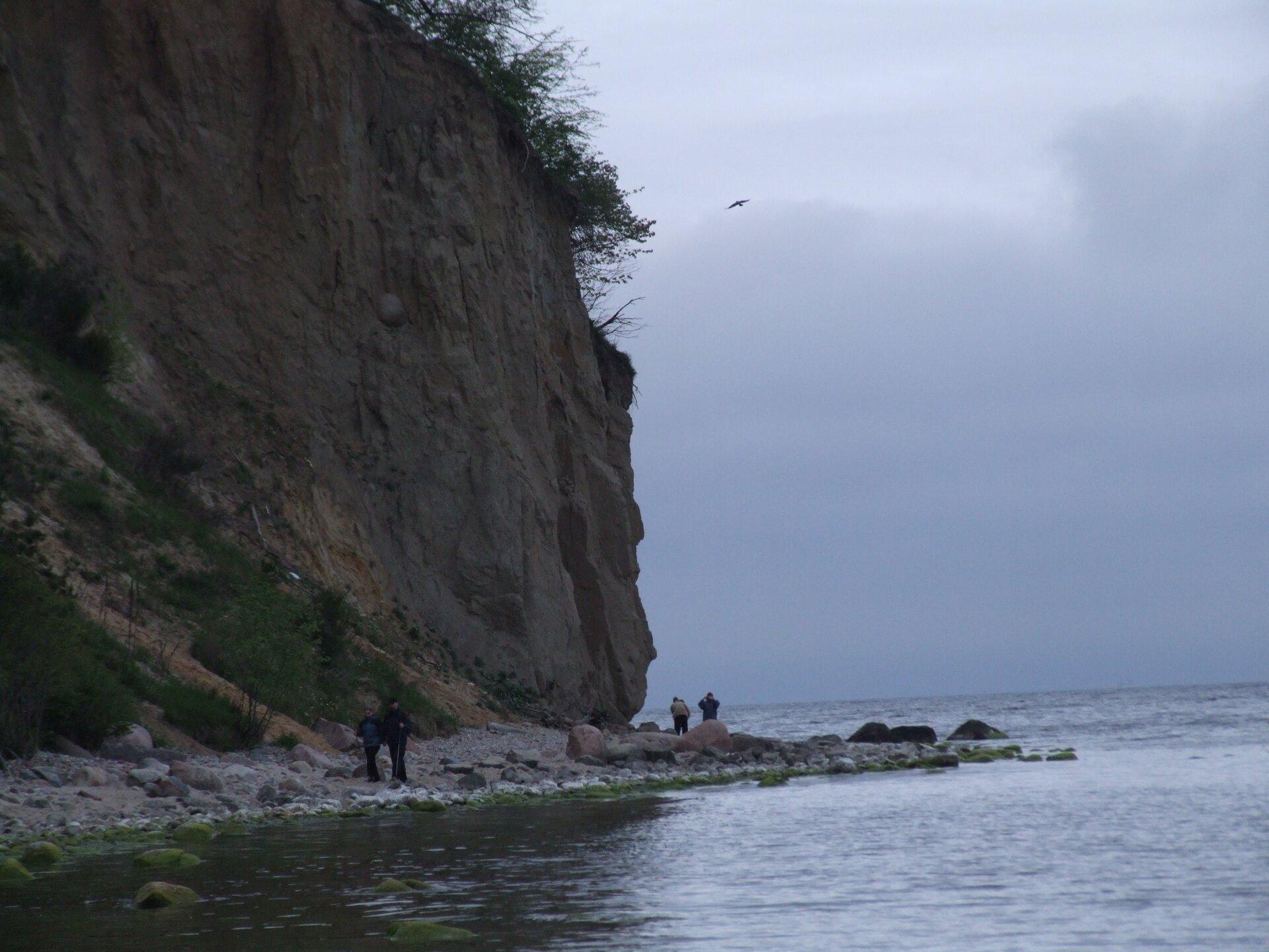 Na zdjęciu wysoki stromy klif, wdole wąska kamienista plaża, spacerowicze.