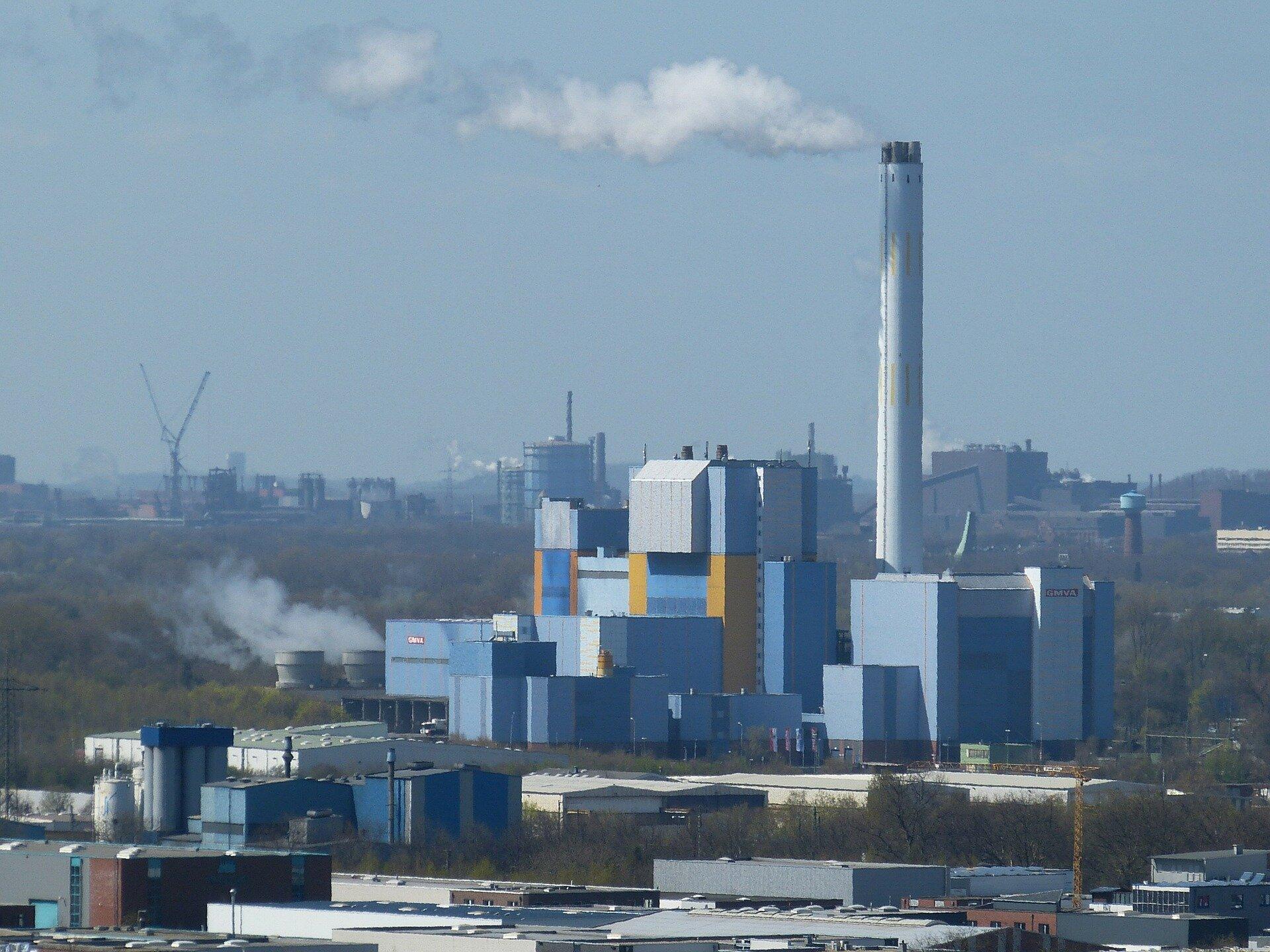 Zdjęcie przedstawia zakład spalania odpadów widoczny zwiększej odległości. Kompleks składa się zkilkunastu pudełkowatych budynków wróżnych kolorach zwidocznym po lewej stronie wysokim kominem zktórego unosi się niewielka ilość białego dymu. Zakład otoczony jest drzewami imagazynami. Daleko wtle na horyzoncie widać duże zagęszczenie zakładów przemysłowych.