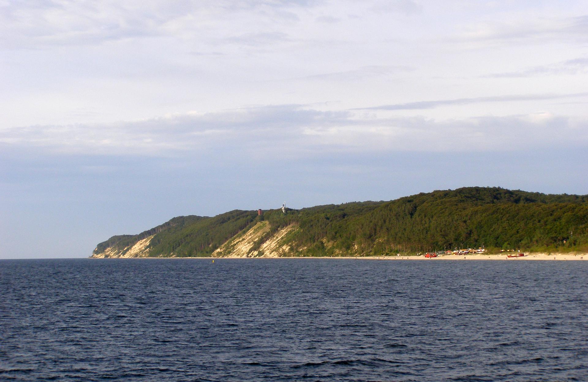 Fotografia przedstawia morze inadmorskie łagodne grzbiety, porośnięte lasem. To klif wWolińskim Parku Narodowym.