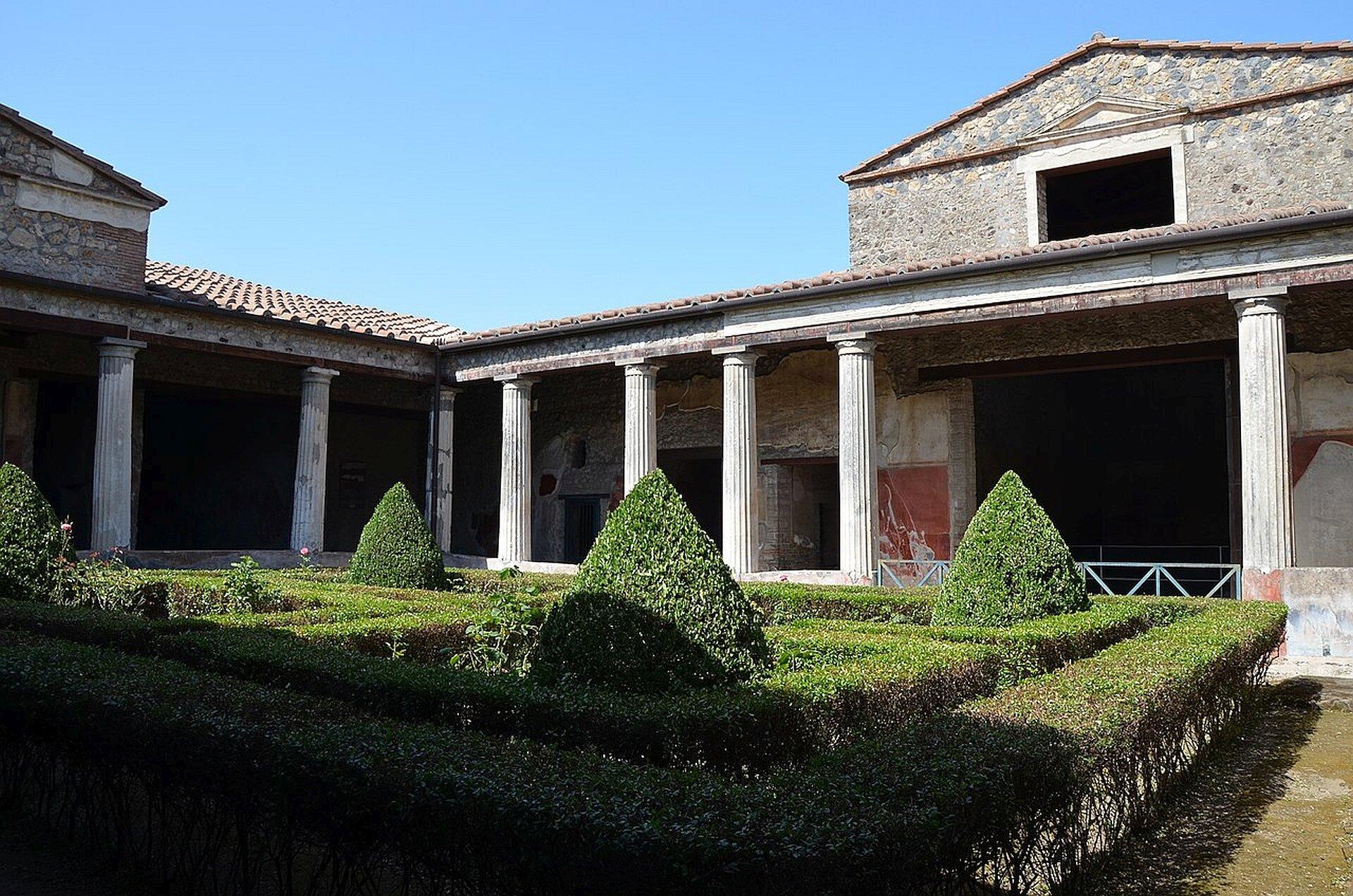 Kolorowa ilustracja przedstawia zewnętrzny widok odrestaurowanego budynku pompejańskiego tzw. domu Menandra. Fotografia ukazuje dwa połączone ze sobą przestronne skrzydła domu. Dom wyposażony jest wkrużganek wsparty białymi żłobkowanymi kolumnami ikryty czerwoną dachówką. Przed domem znajduje się perystyl zzadbaną zielenią.
