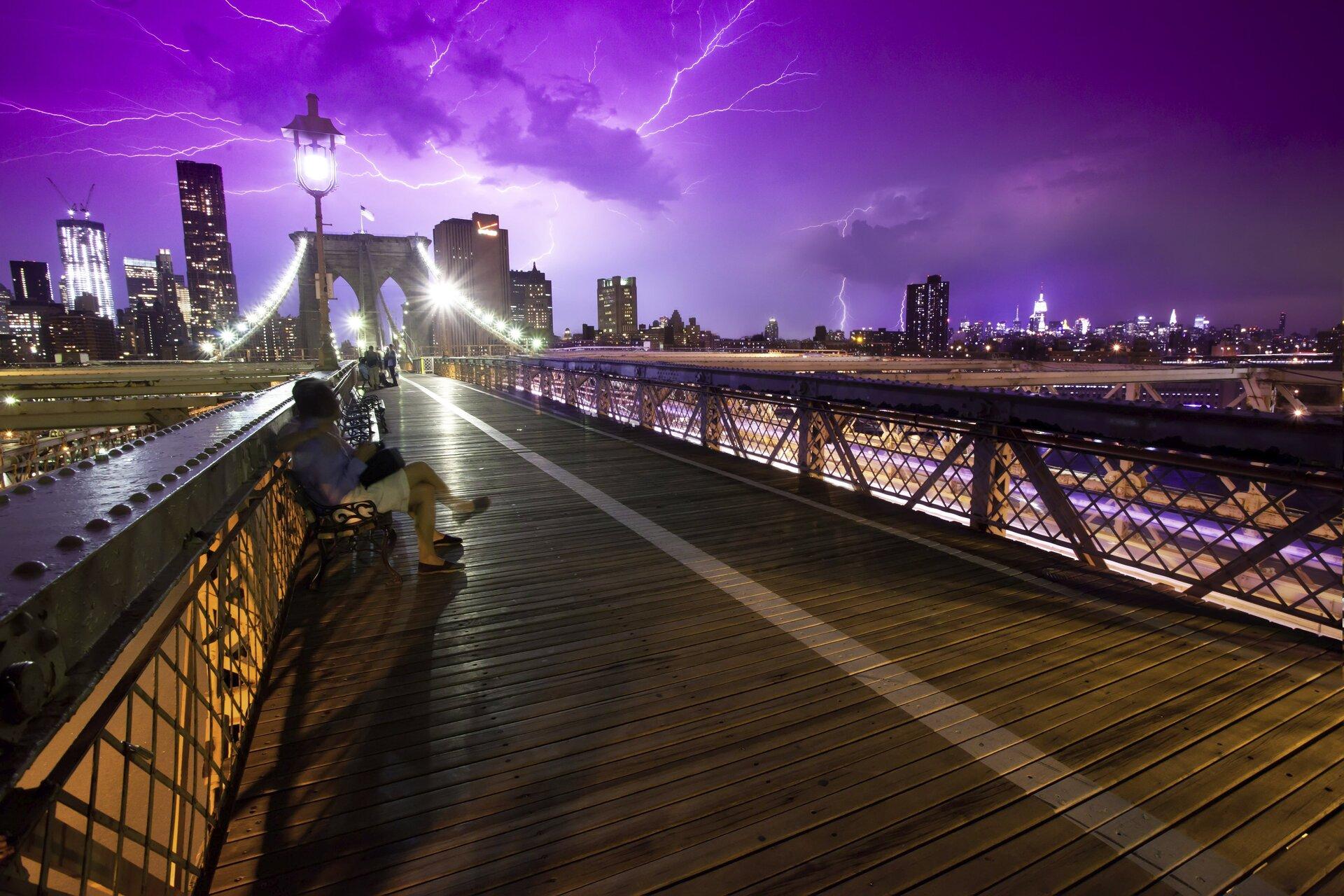 Zdjęcie przedstawia niecodzienną scenę. Noc, panorama Nowego Jorku zmostem brooklyńskim wcentrum kadru. Daleko wtle światła Manhattanu, na pierwszym planie pomost zławkami na przedłużeniu którego woddali znajduje się centralna część mostu. Pierwsza ławka zajęta przez siedzącą na niej kobietę. Widoczne światła wielkiego miasta oraz oświetlenie mostu ilatarnie przy kładce. Niebo pochmurne wkolorze fioletu, całe poprzecinane błyskawicami odległej burzy.