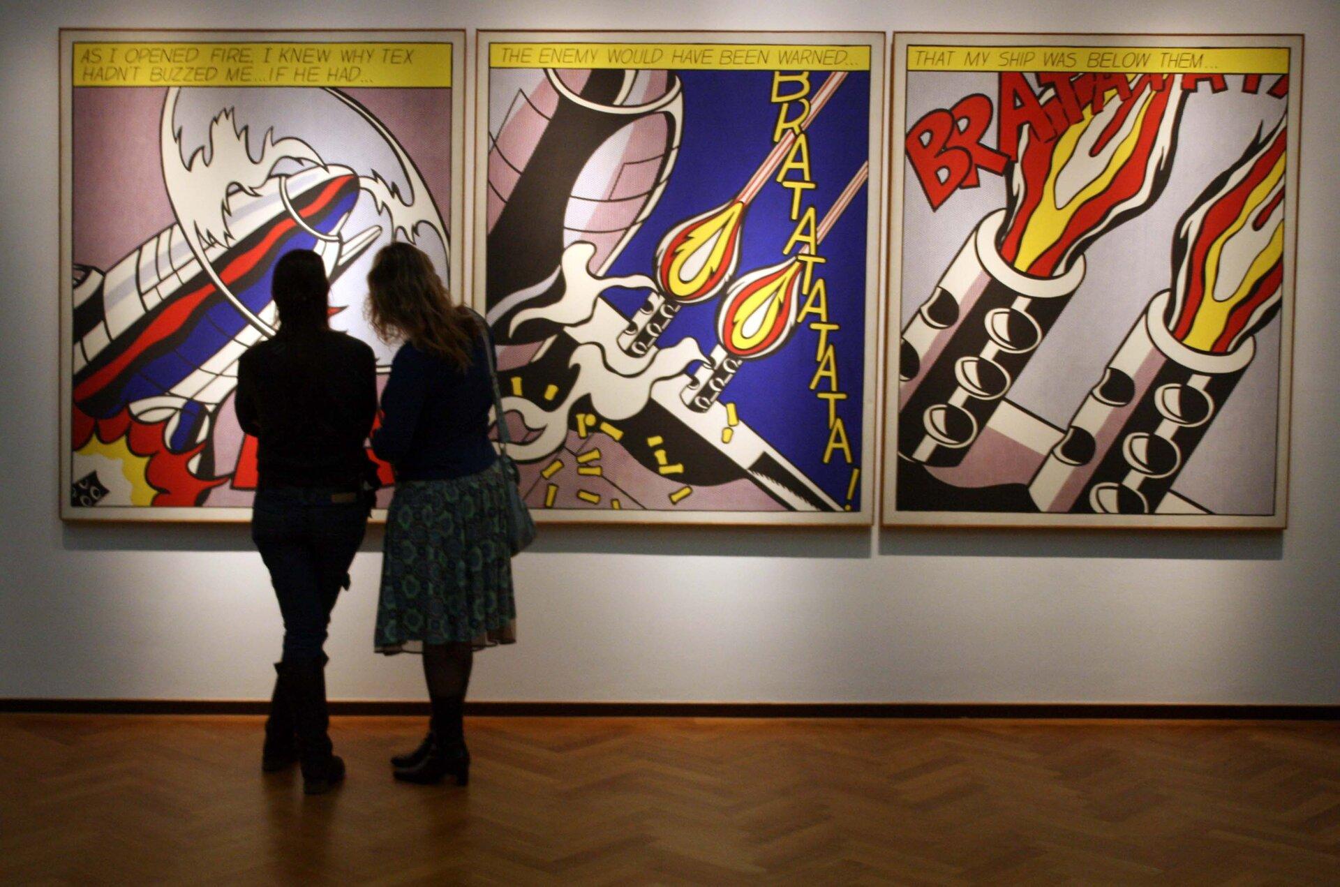 """Ilustracja przedstawia zdjęcie zgalerii przedstawiające dzieło Roya Lichtensteina """"As IOpened Fire"""", ukazujące dwie postacie stojące przed obrazami artysty. Na ścianie wiszą trzy obrazy. Pierwszy przedstawia fragment samolotu zkręcącym się śmigłem. Drugi fragment skrzydła, zktórego wystrzeliwane są pociski. Trzeci jest zbliżeniem na pociski."""