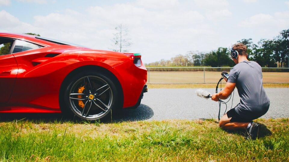 Zdjęcie przedstawia sportowy czerwony samochód oraz mężczyznę, który przy nim przykucnął. Ma on słuchawki na uszach. Wjednej ręce trzyma mikrofon, awdrugiej urządzenie przypominające dyktafon. Mikrofon jest skierowany wstronę samochodu, azatem mężczyzna najprawdopodobniej nagrywa dźwięk, jaki wydaje silnik.