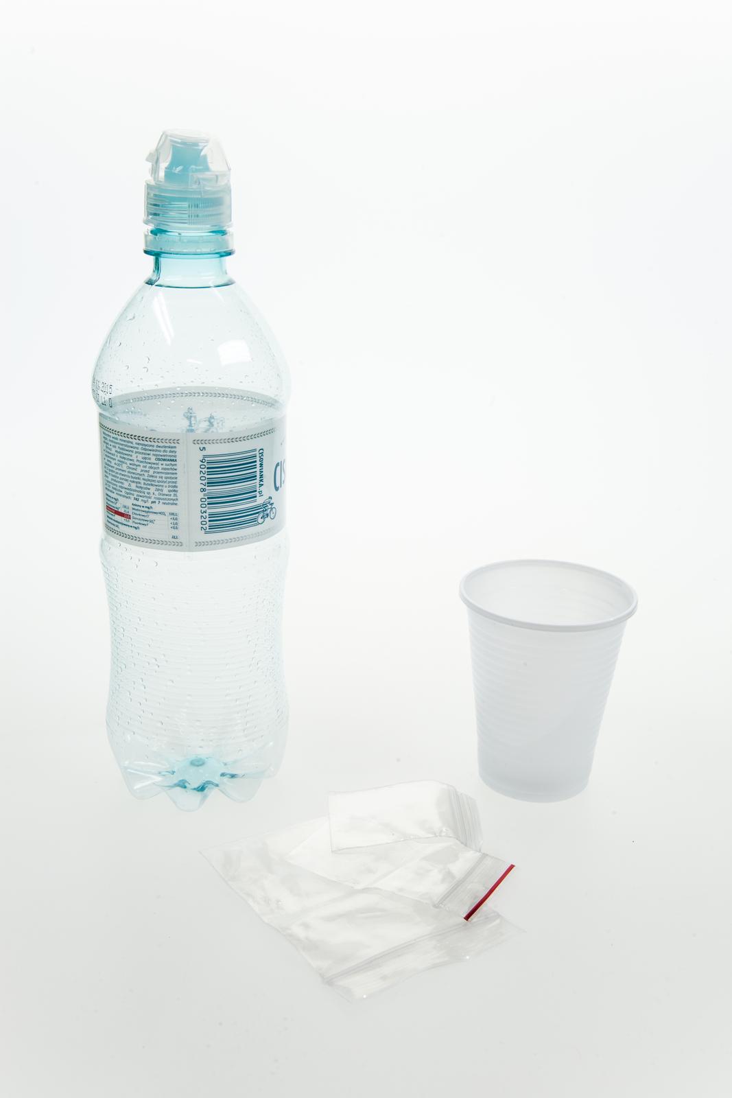 Fotografia przedstawia plastikową butelkę, plastikowy kubek iworeczki foliowe.