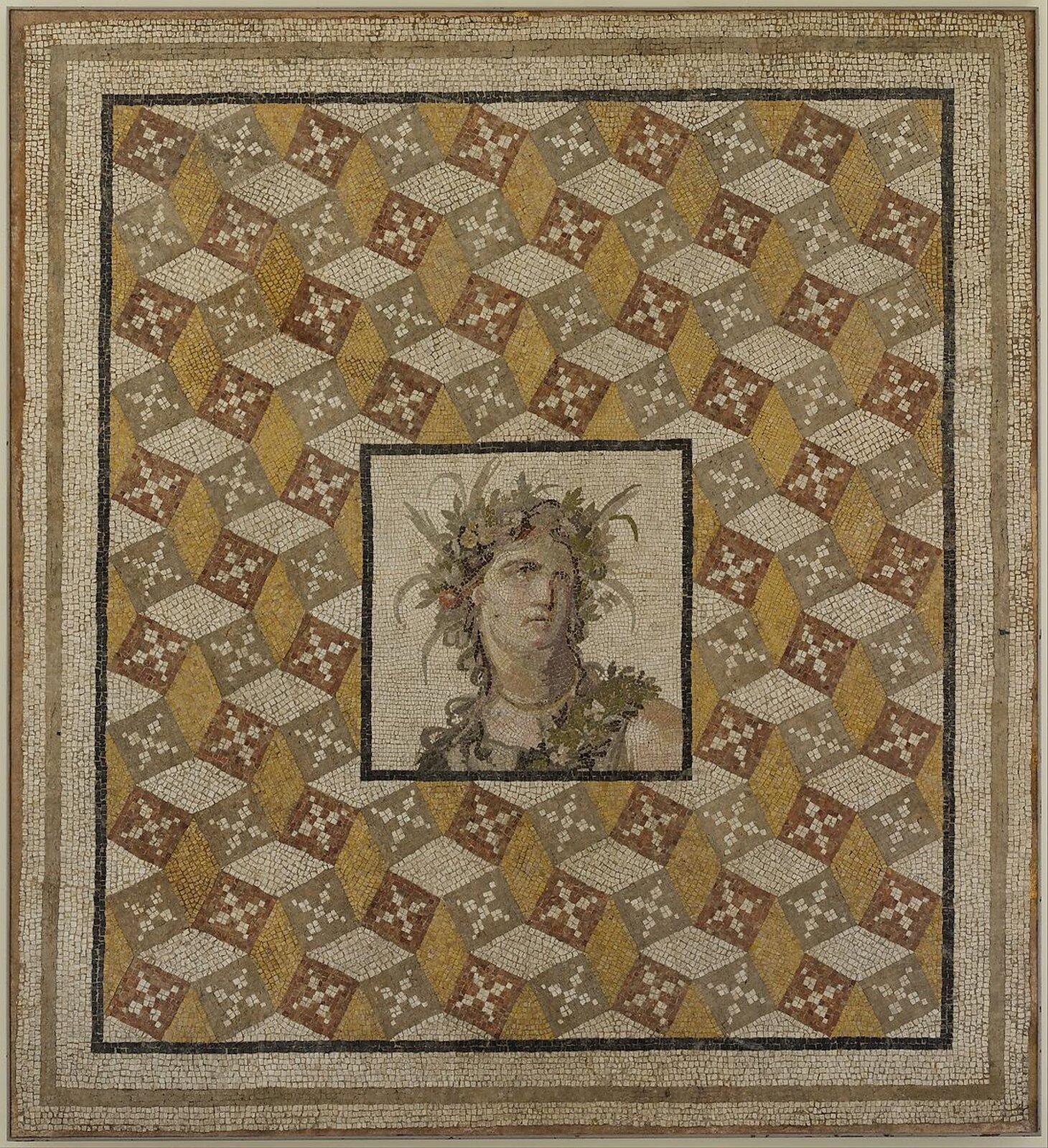 Mozaika podłogowa przedstawia postać nieznanego młodego mężczyzny. Pozuje on zpółprofilu ispogląda wprawą stronę. Na jego głowie widoczny jest duży wianek wykonany zróżnych liści iowoców.