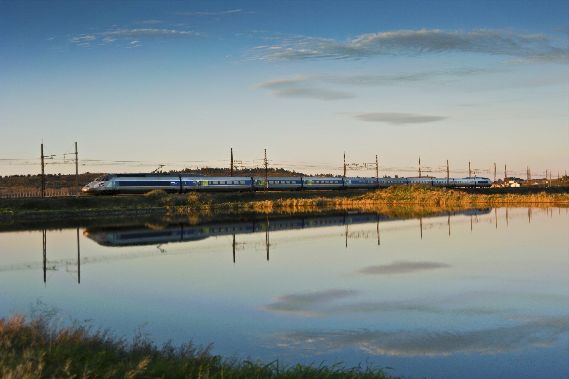 Zdjęcie przedstawia jadący po torach szybki pociąg pasażerski uwieczniony wmomencie mijania akwenu wodnego. Ztego powodu obraz pociągu odbija się wtafli wodnej. Daleko wtle widoczne są zabudowania mieszkalne iwzgórza, anad nim czyste niebo.