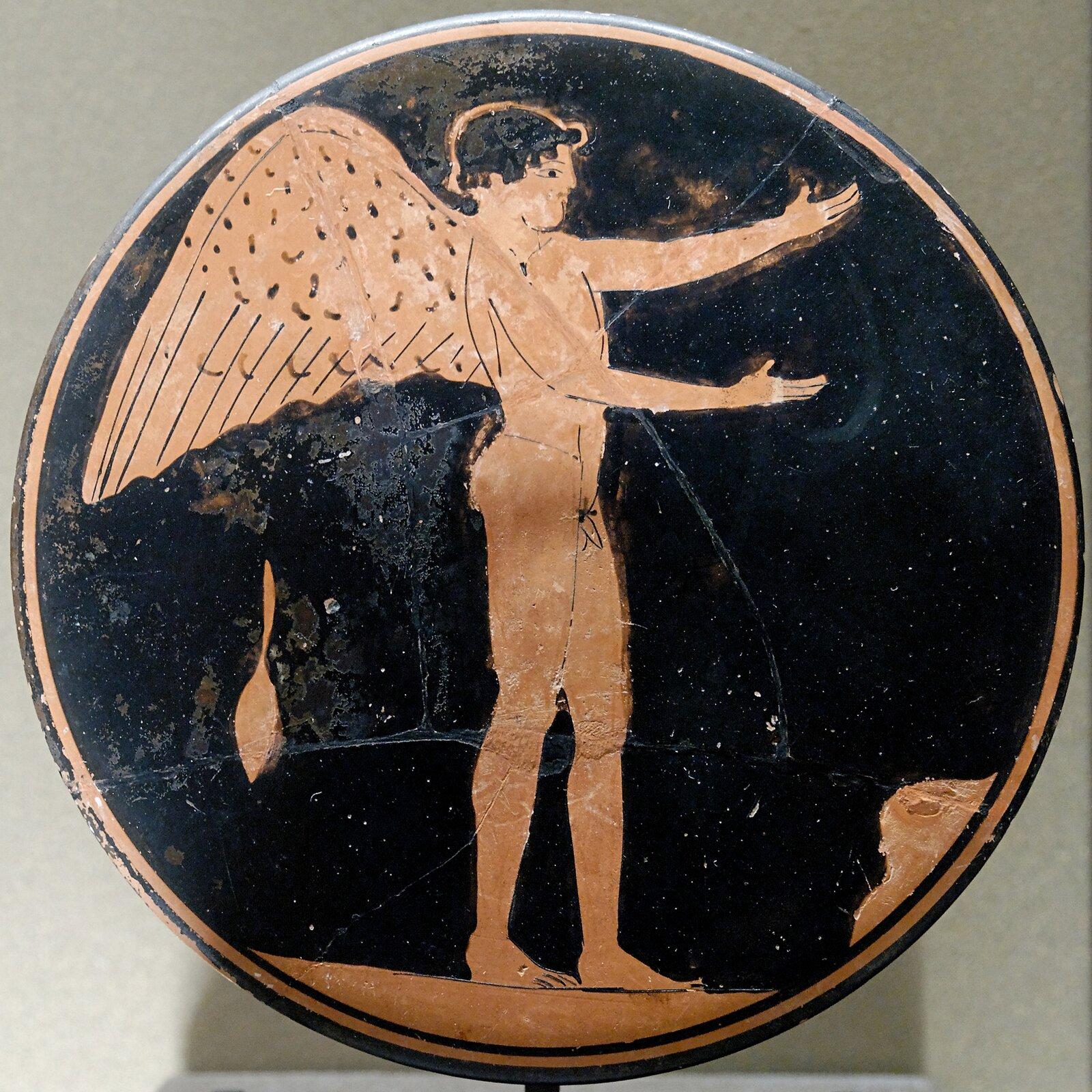 Ilustracja przedstawia paterę zwizerunkiem Erosa - boga miłości. Jest wykonana techniką malarstwa czerwonofigurowego, którym zdobiono naczynia wstarożytnej Grecji. Na czarnym tle ukazany jest stojący, nagi iuskrzydlony Eros. Obie ręce ma wyciągnięte prze siebie. Patera otoczona jest oblamówką.
