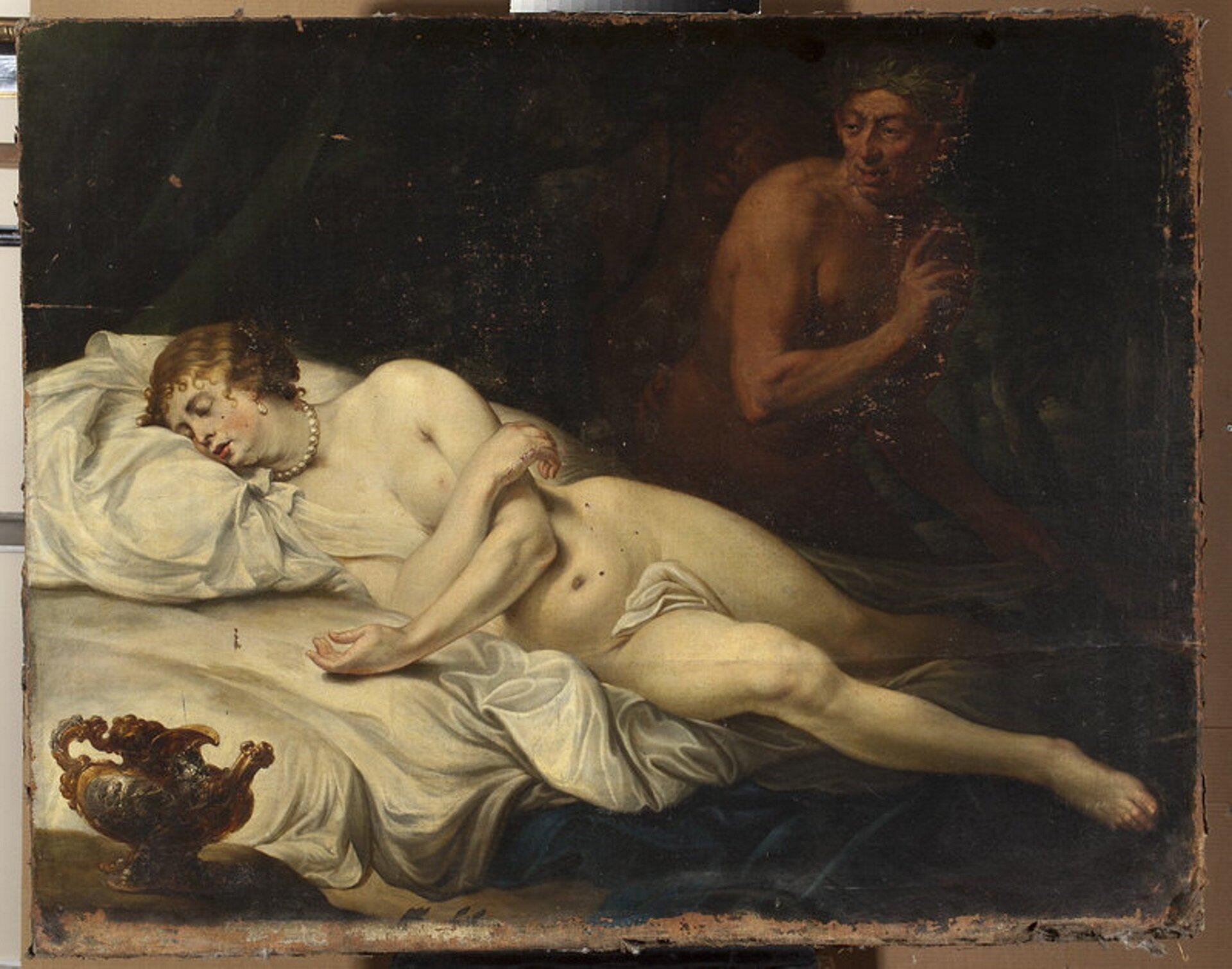 """Ilustracja przedstawia obraz nieznanego malarza flamandzkiego """"Śpiąca Wenus zSatyrem"""". Na obrazie widzimy nagą, śpiącą na łóżku kobietę zkoralami na szyi. Ułożona jest na poduszce iudrapowanej pościeli. Wlewym rogu stoi orientalny dzban. Za Wenus czai się Satyr. Spogląda na Wenus. Jego postać ukryta jest wciemności. Tło jest ciemnobrązowe."""