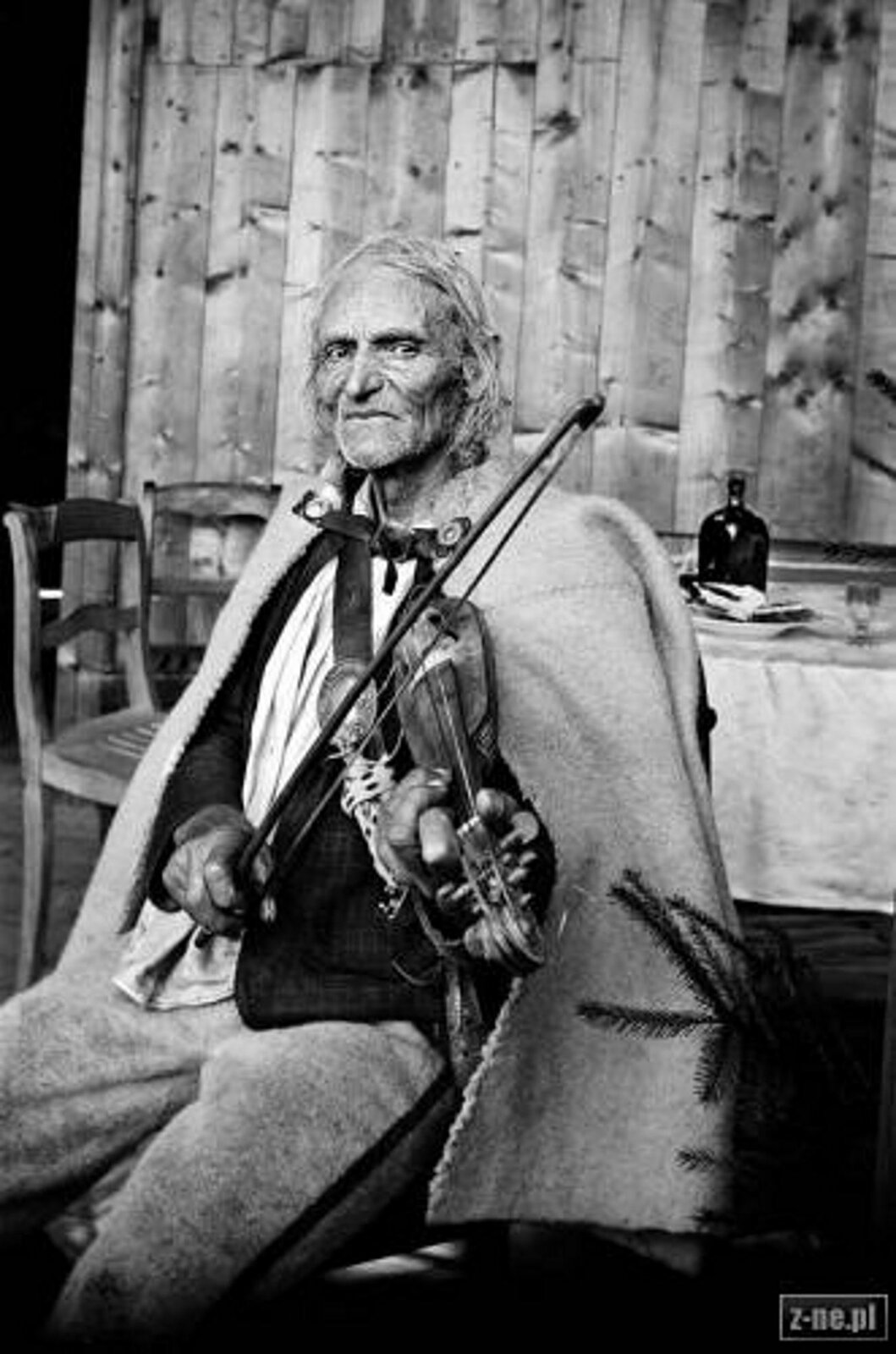 Fotografia przedstawia Jana Krzeptowskiego – legendarny Sabała, najsłynniejszy podhalański skrzypek. Starszy mężczyzna zuśmiechem, siedzi igra na skrzypcach. Ubrany jest wstrój góralski.